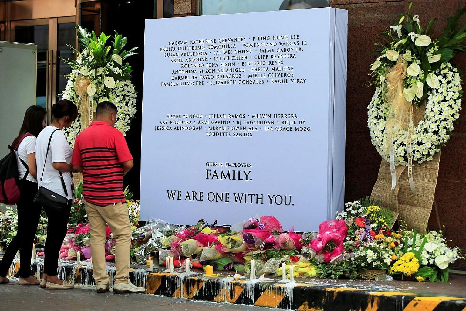 Employees paying their respects to those killed in the casino fires, at a memorial at Resorts World Manila on Sunday. Gunman Jessie Javier Carlos set alight a number of rooms at the complex, claiming the lives of 37 people.