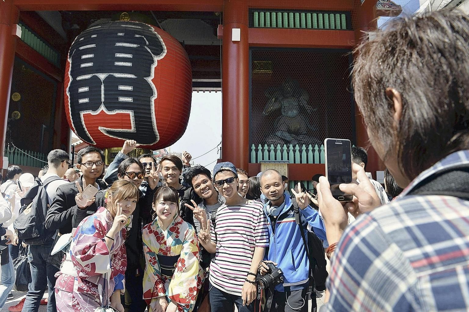 Tourists in front of the Kaminarimon gate in the Asakusa area of Tokyo. Japan has been rewriting tourism records for four straight years, drawing a high of 24 million tourists last year.