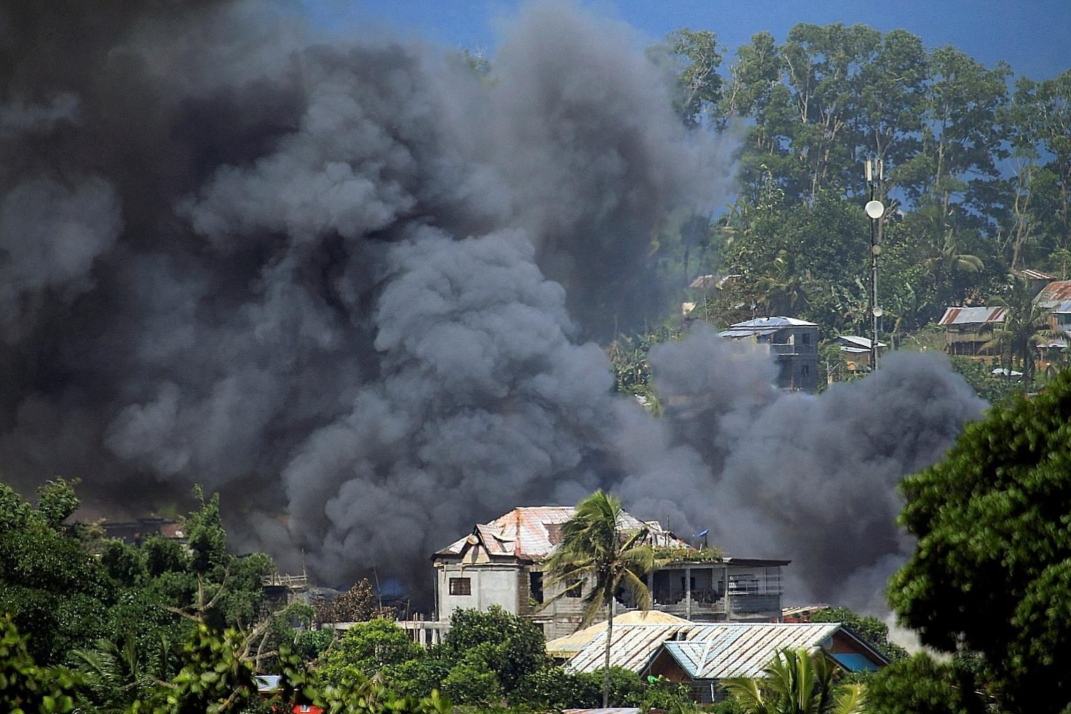 An aircraft launching a rocket during an air strike against the ISIS-linked Maute group in Marawi yesterday. The city (top) has become a battleground as the Philippine military continues its assault on the militants.