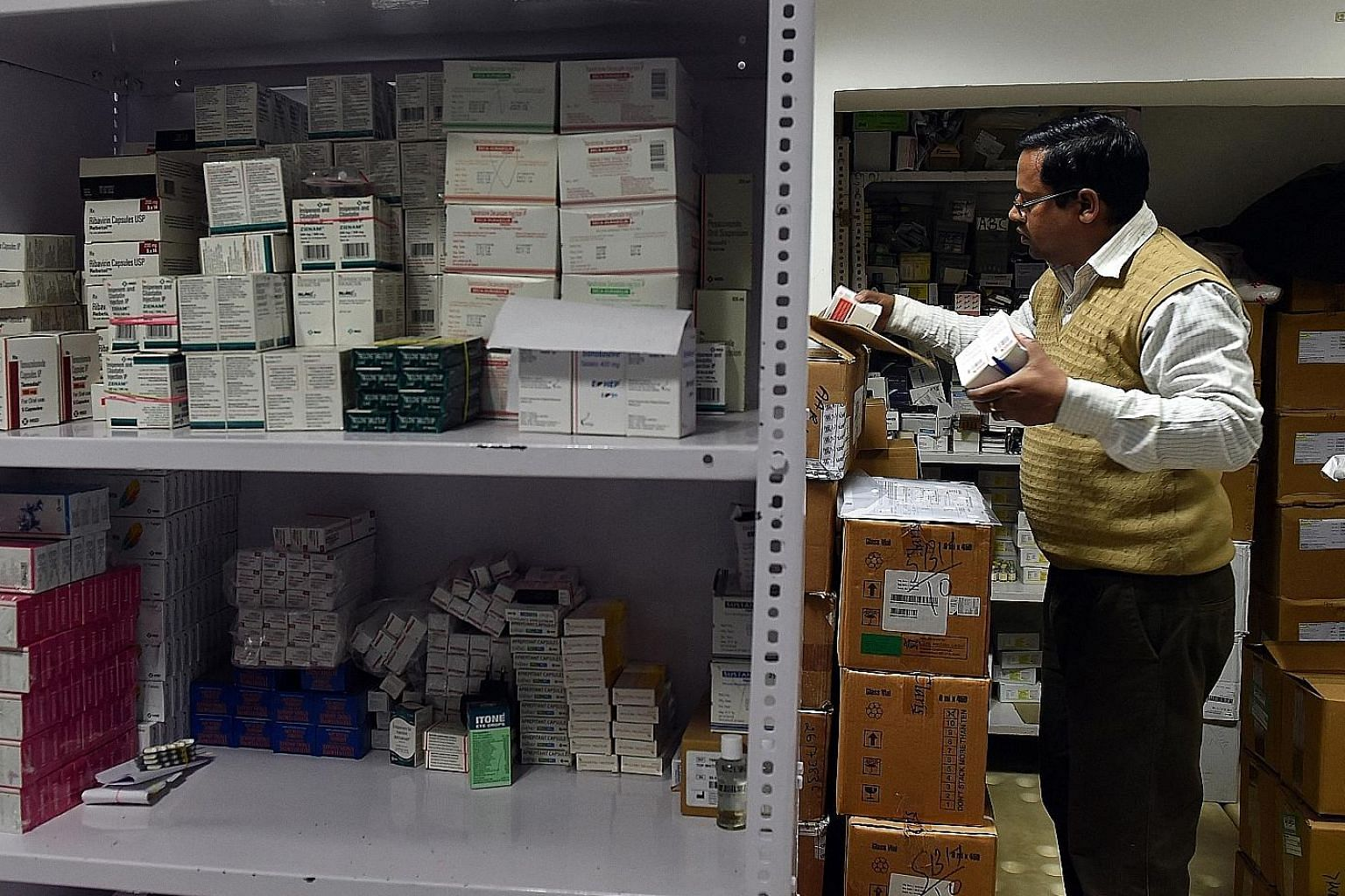 A pharmacy employee gathers drugs for a customer in New Delhi. The government is formulating regulation for online pharmacies, but there have been complaints that these pharmacies are undercutting the business of their bricks-and- mortar rivals throu