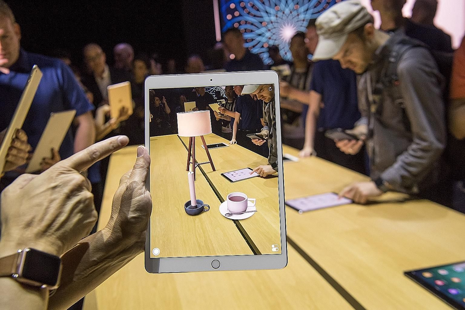 A participant checking out the ARKit augmented reality tool on a new iPad Pro at the Apple Worldwide Developers Conference in San Jose, California, last week. The 10.5-inch iPad Pro is powered by the new Apple A10X Fusion chip, which Apple claims is