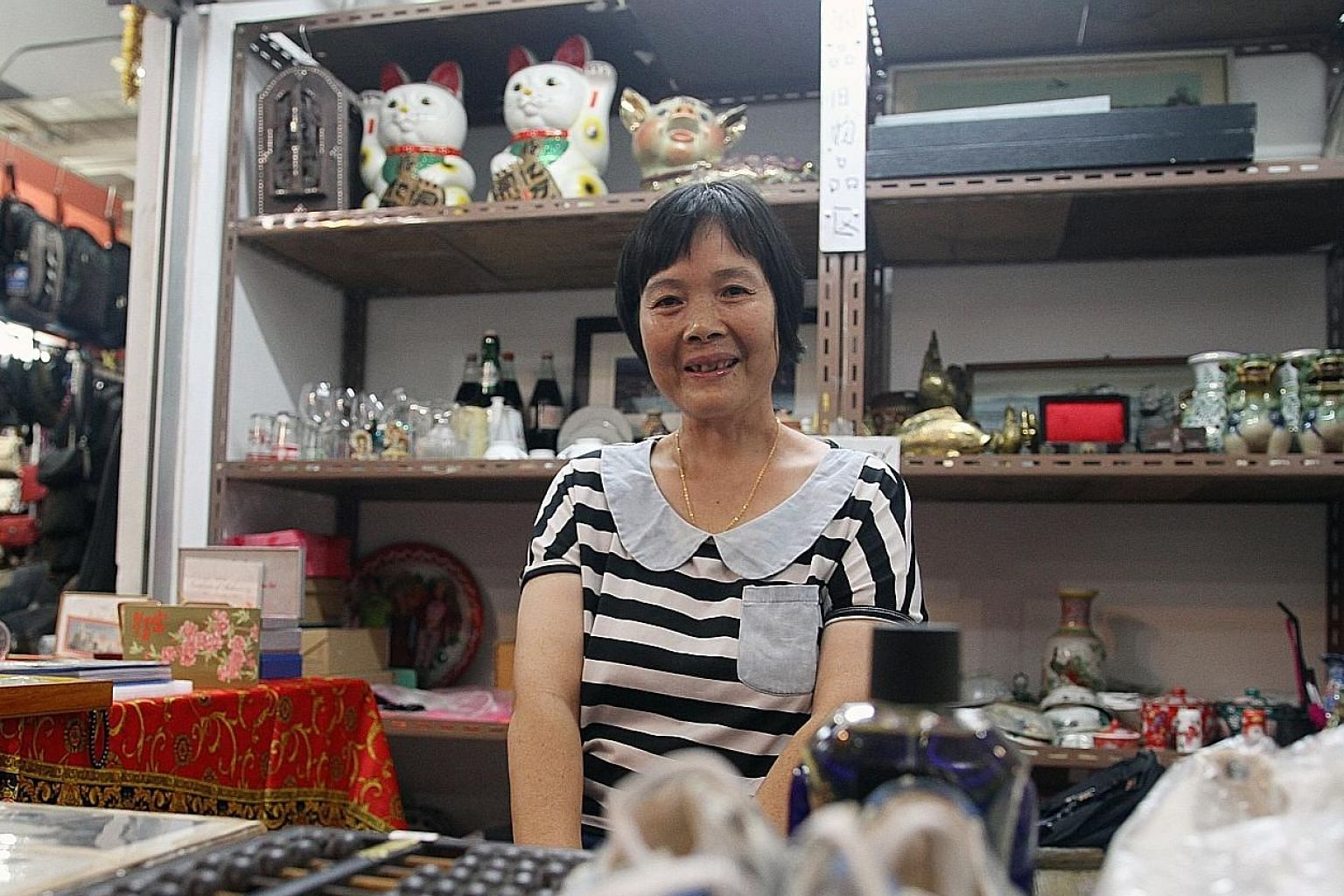 Madam Tan Guo Mei at her new stall at Chinatown Market. She is one of the beneficiaries of the assistance provided to Sungei Road vendors. Besides selling second-hand collectibles, she has started selling new shoes at her stall, which opened for busi