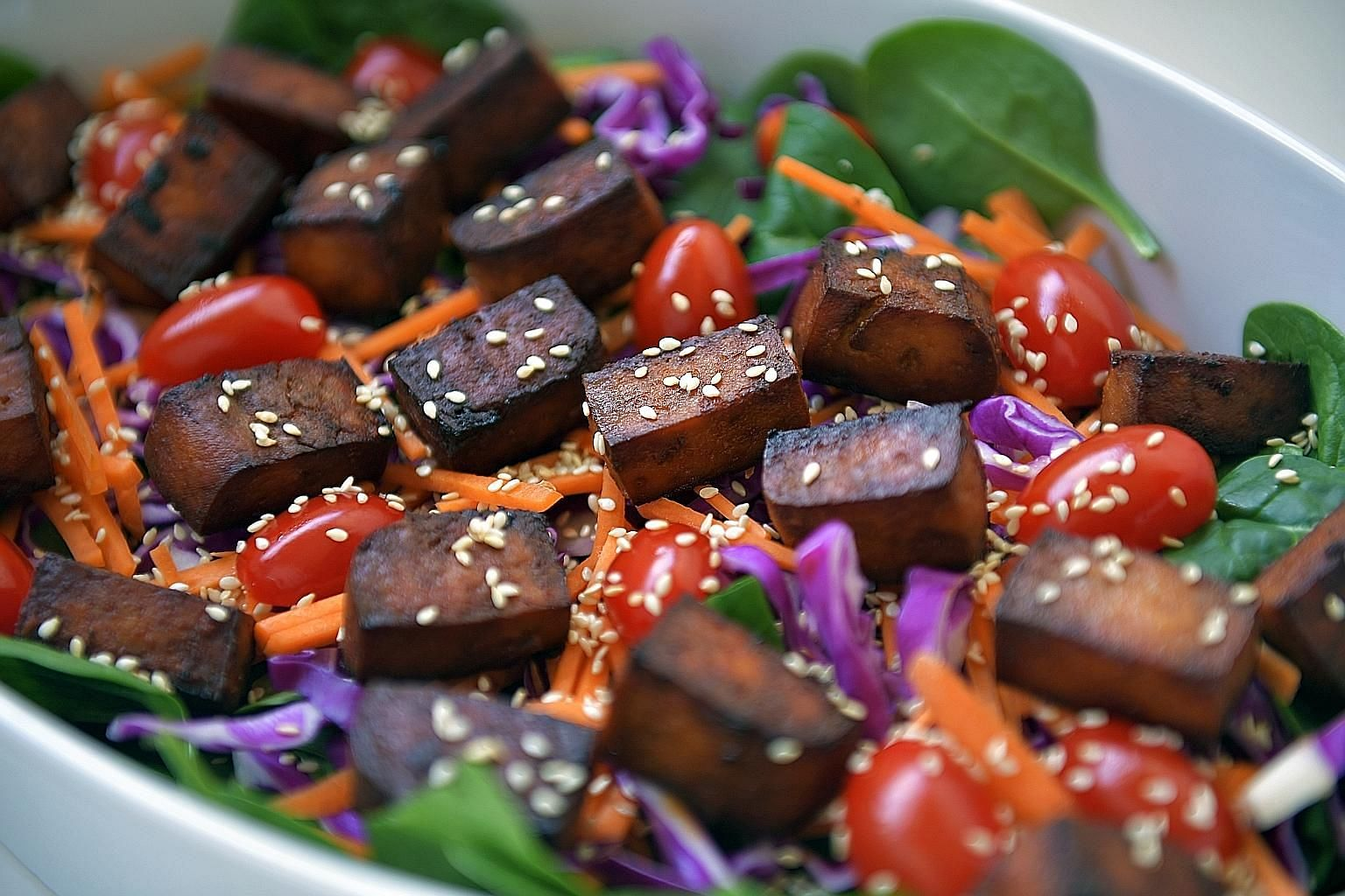 Serve the baked tofu with baby spinach, julienned carrots, purple cabbage and grape tomatoes for a healthy meal.