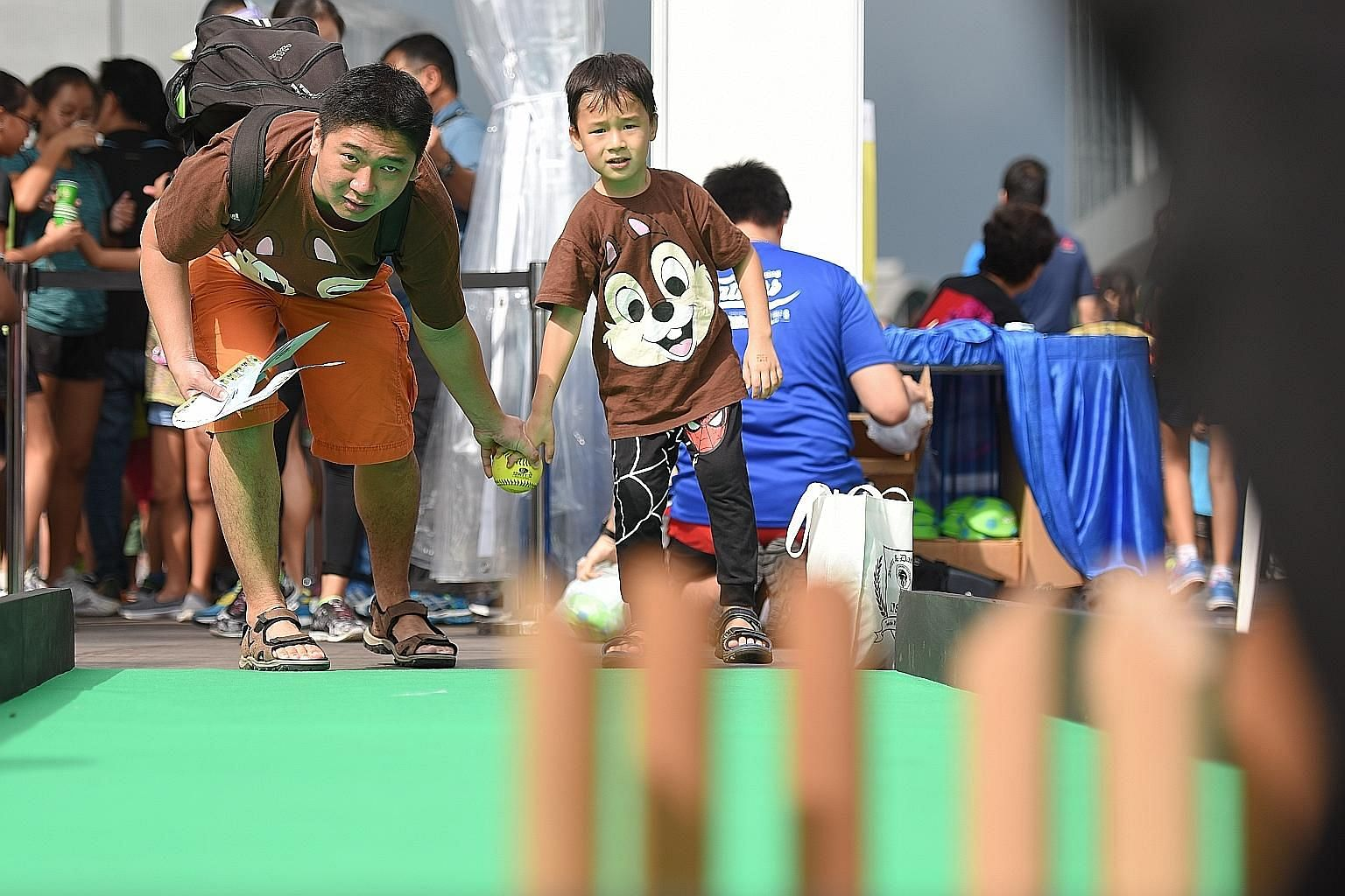 Mr Daniel Chua, 38, a logistics assistant, playing mini bowling with his son Ocean, six, at the Father's Day carnival yesterday.