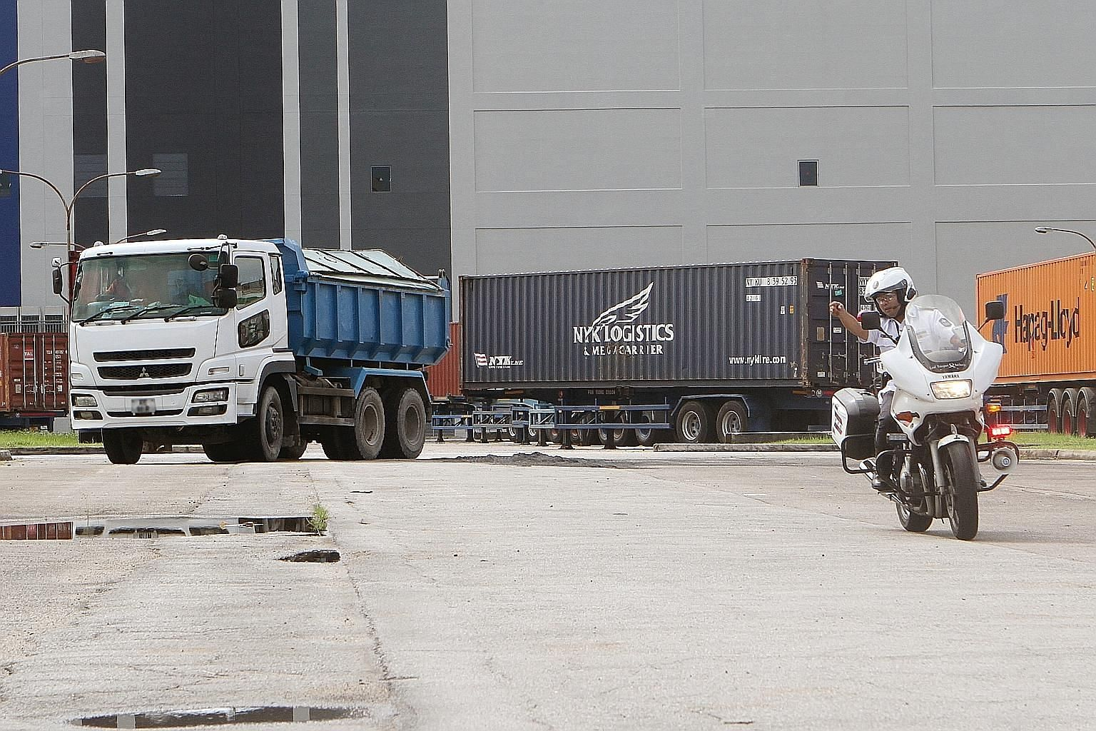A traffic policeman directing a driver suspected of carrying an overweight load to a spot for inspection yesterday. The blitz by police, LTA and NEA targeted errant drivers after a series of fatal accidents involving heavy vehicles.