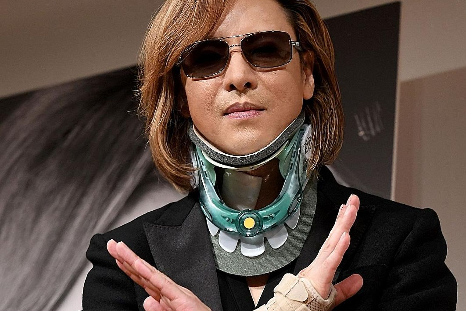 Yoshiki in a neck brace on Tuesday at his first press conference since emergency surgery to implant an artificial cervical disc.