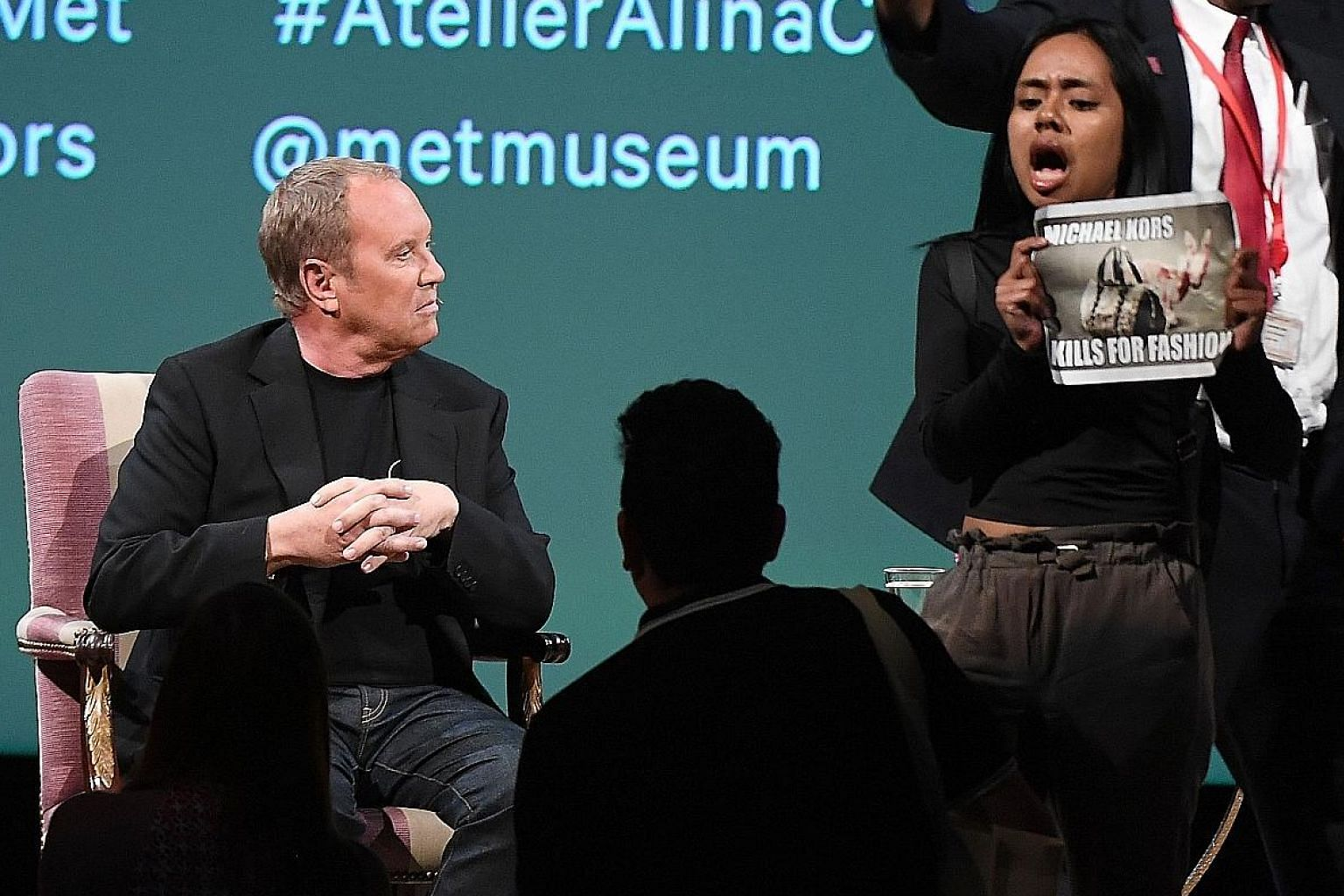 Fashion designer Michael Kors (above left) at the interview, which was disrupted by a protest.