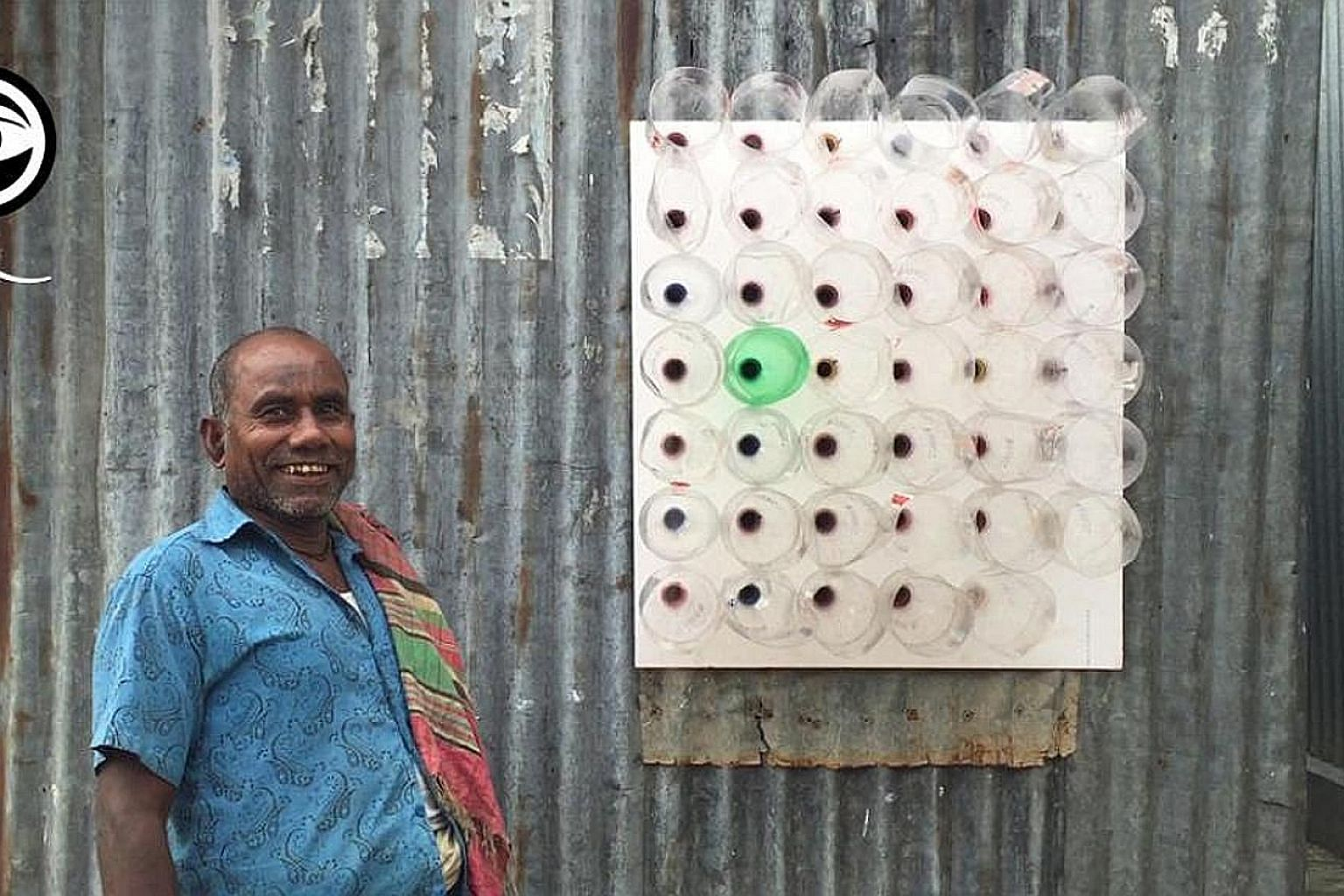 An Eco-Cooler - made of cut plastic bottles mounted on a board with the cut ends facing outside - installed in a window. Hot air entering the bottles is compressed in the bottlenecks, which cools it before it enters the house.