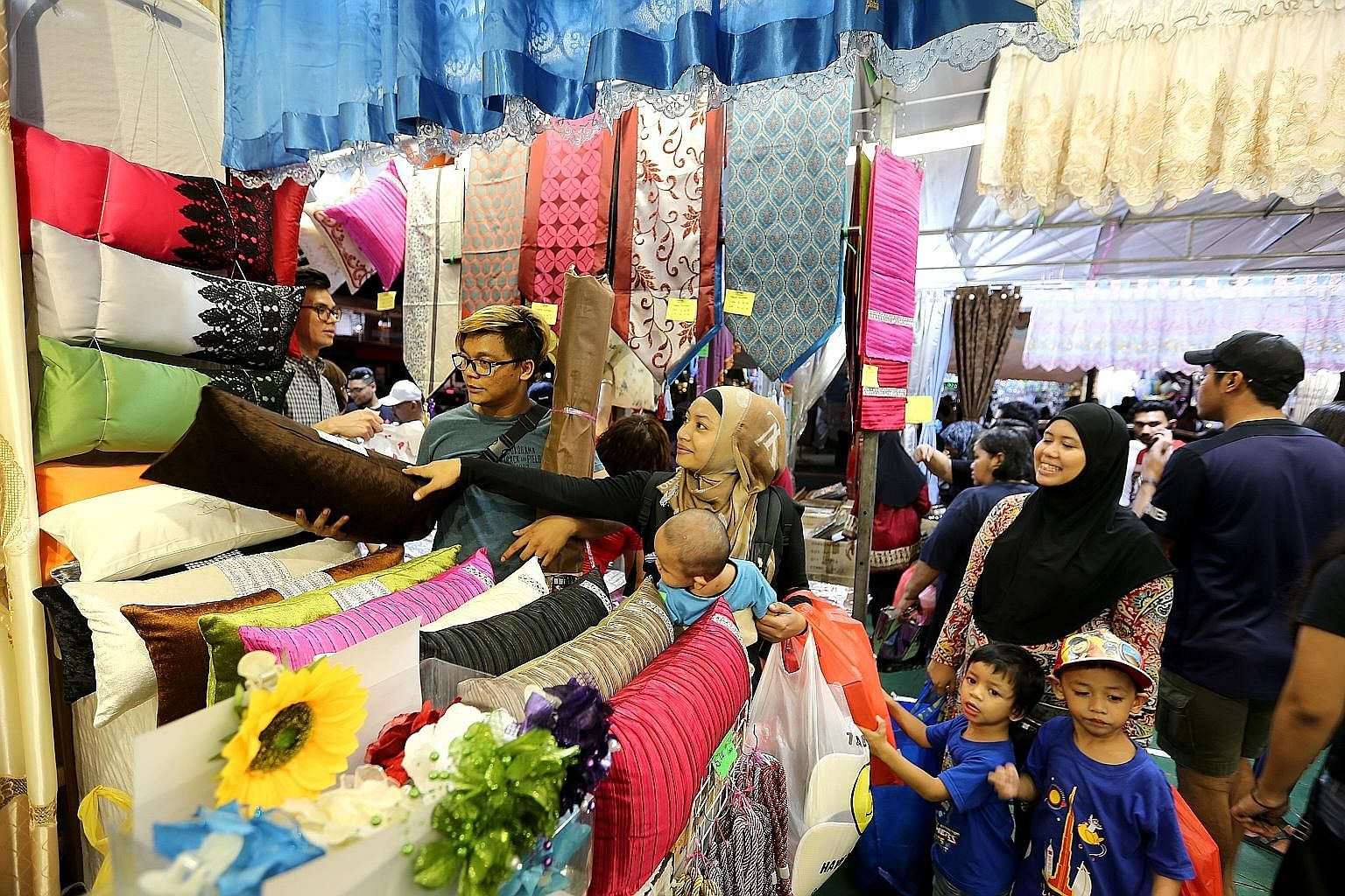 Madam Fatin Shazwani (centre) and her family getting some last-minute Hari Raya Aidilfitri shopping done at the Geylang Serai Bazaar last night. The month-long bazaar, which was into its final night, was jam-packed with people hoping to pick up barga