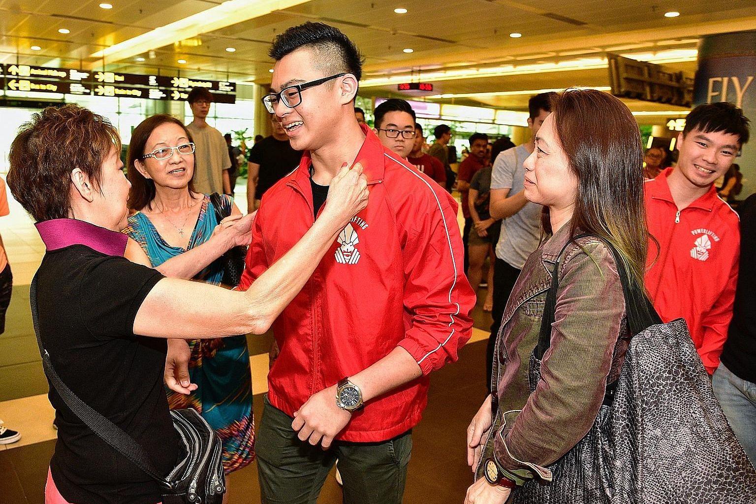 Powerlifter Matthew Yap greeting his grandaunt Mary Chua at the airport while his mother Ophelia Lim (second from right) looks on. Matthew returned with his brother Marcus (right). Singaporean Matthew Yap set a new world record with a 208kg squat in