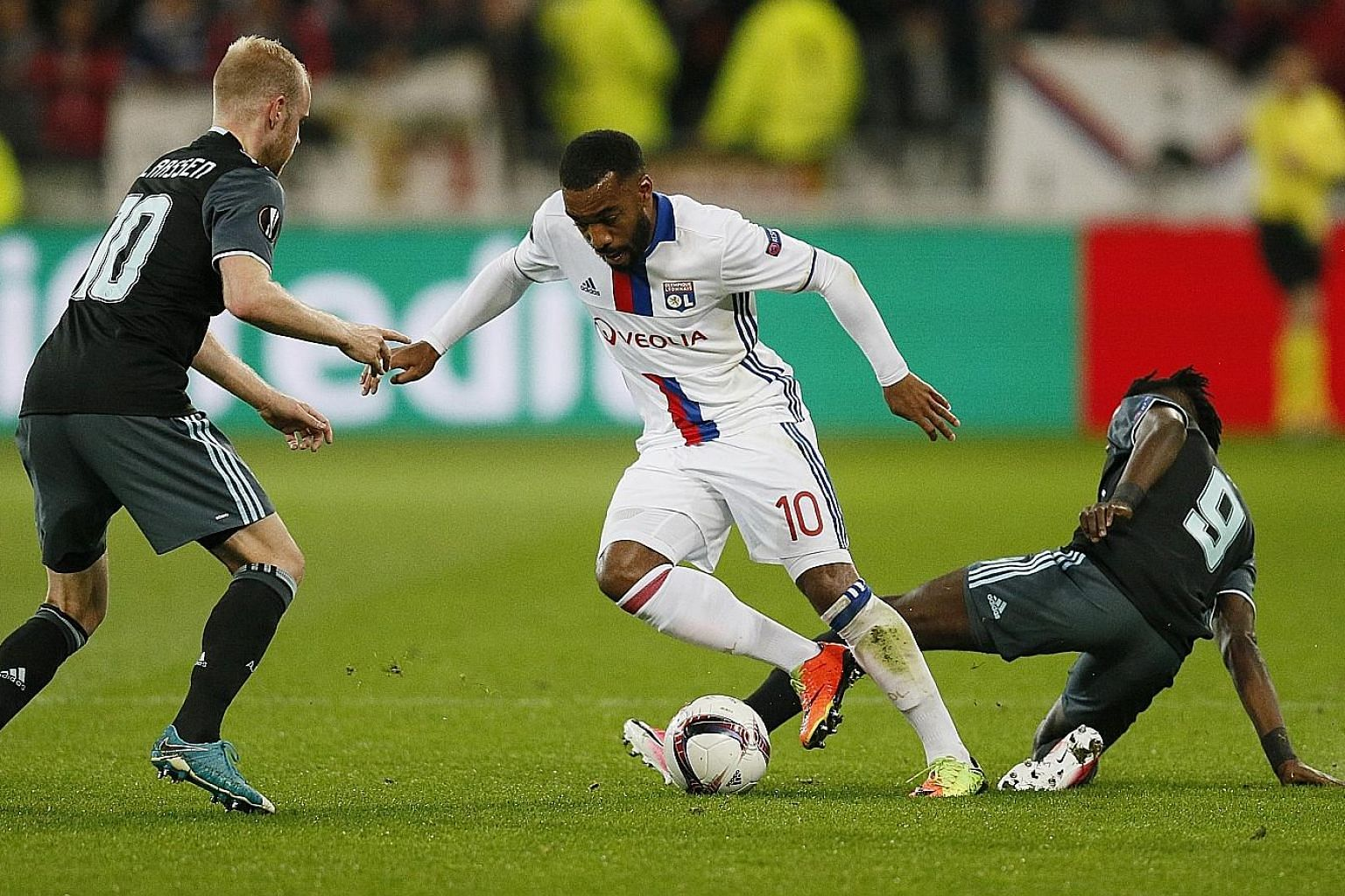 Lyon's Alexandre Lacazette (centre) takes on Ajax's Davy Klaassen after evading Bertrand Traore (right) in the Europa League semi-final last month. Arsenal are believed to be the front-runners in the race to sign the France international.
