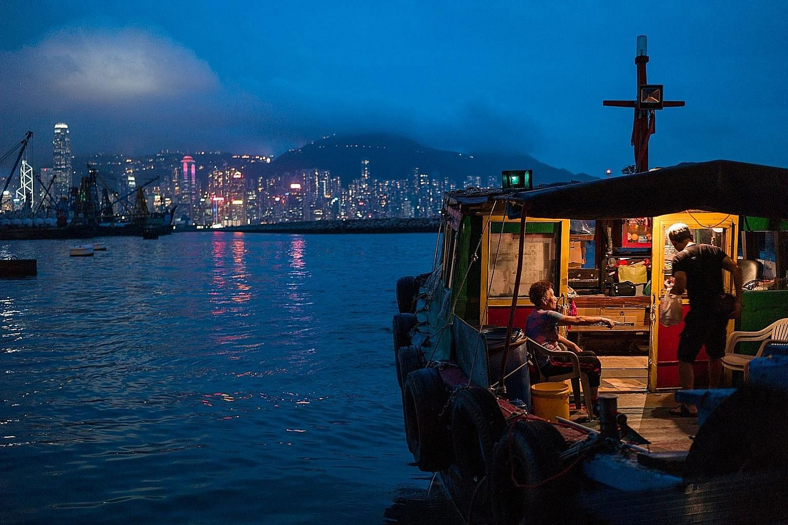 "A couple in their junk in a typhoon shelter in Hong Kong's Kowloon peninsula. Good jobs, better social benefits, more affordable housing, and an assurance to protect the existing lifestyle will help preserve the ""one country, two systems"" framework w"