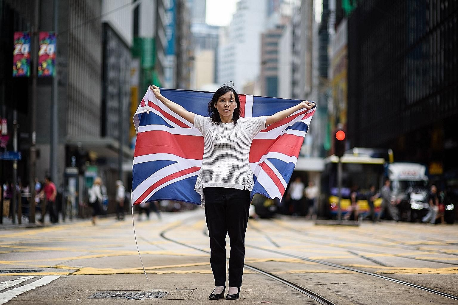 "Hong Kong artist and designer Alice Lai, 39, who heads a small protest group called HK-UK Reunification Campaign, with the British flag. Ms Lai, who regularly flies Hong Kong's former colonial flag at political rallies, said: ""Hong Kong and the UK co"
