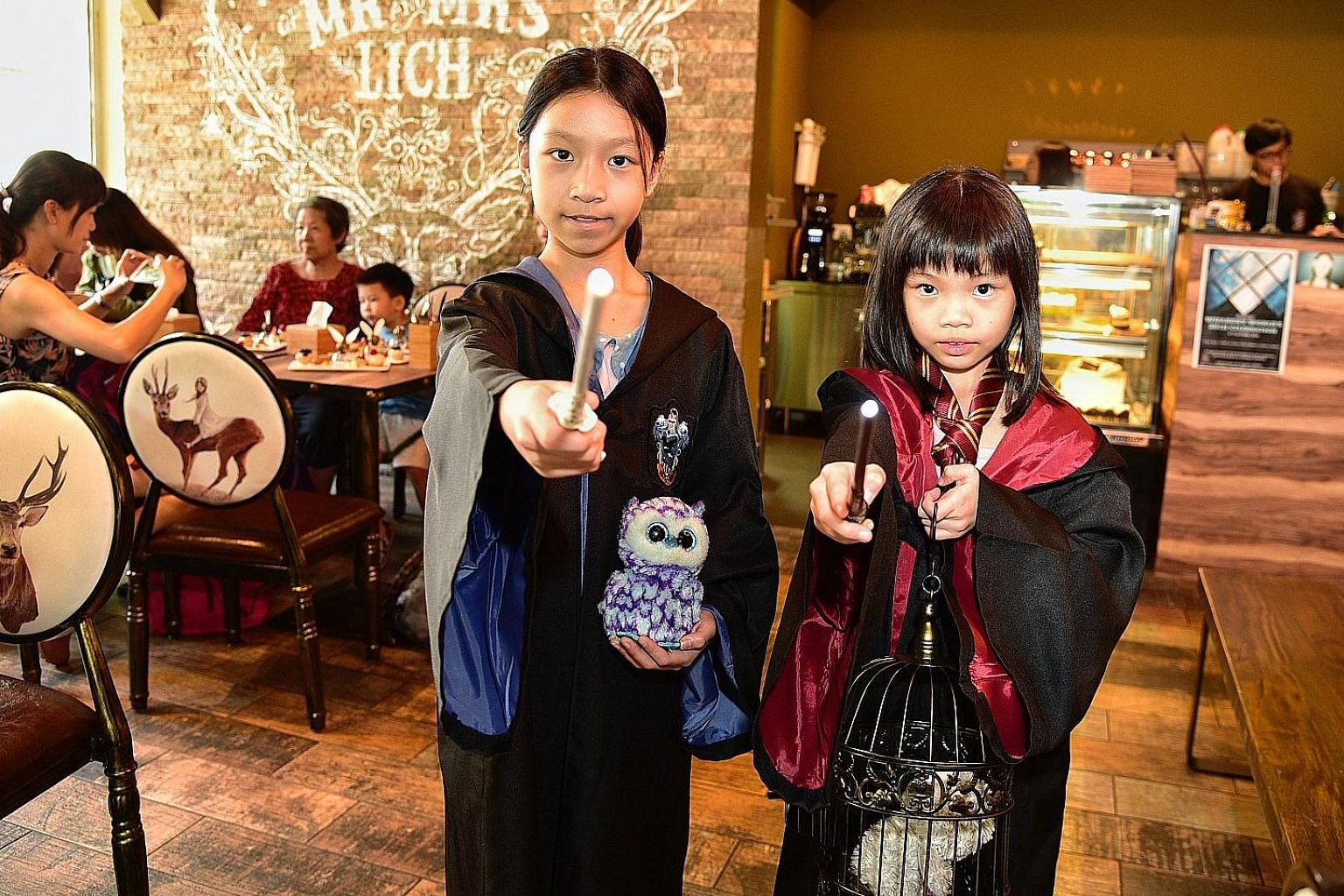 Sisters Faith and Noelle Ow Yong, who are 10 and eight, at a Harry Potter tea party at wizard- themed cafe Platform 1094 to mark the 20th anniversary of the publication of Harry Potter And The Philosopher's Stone.