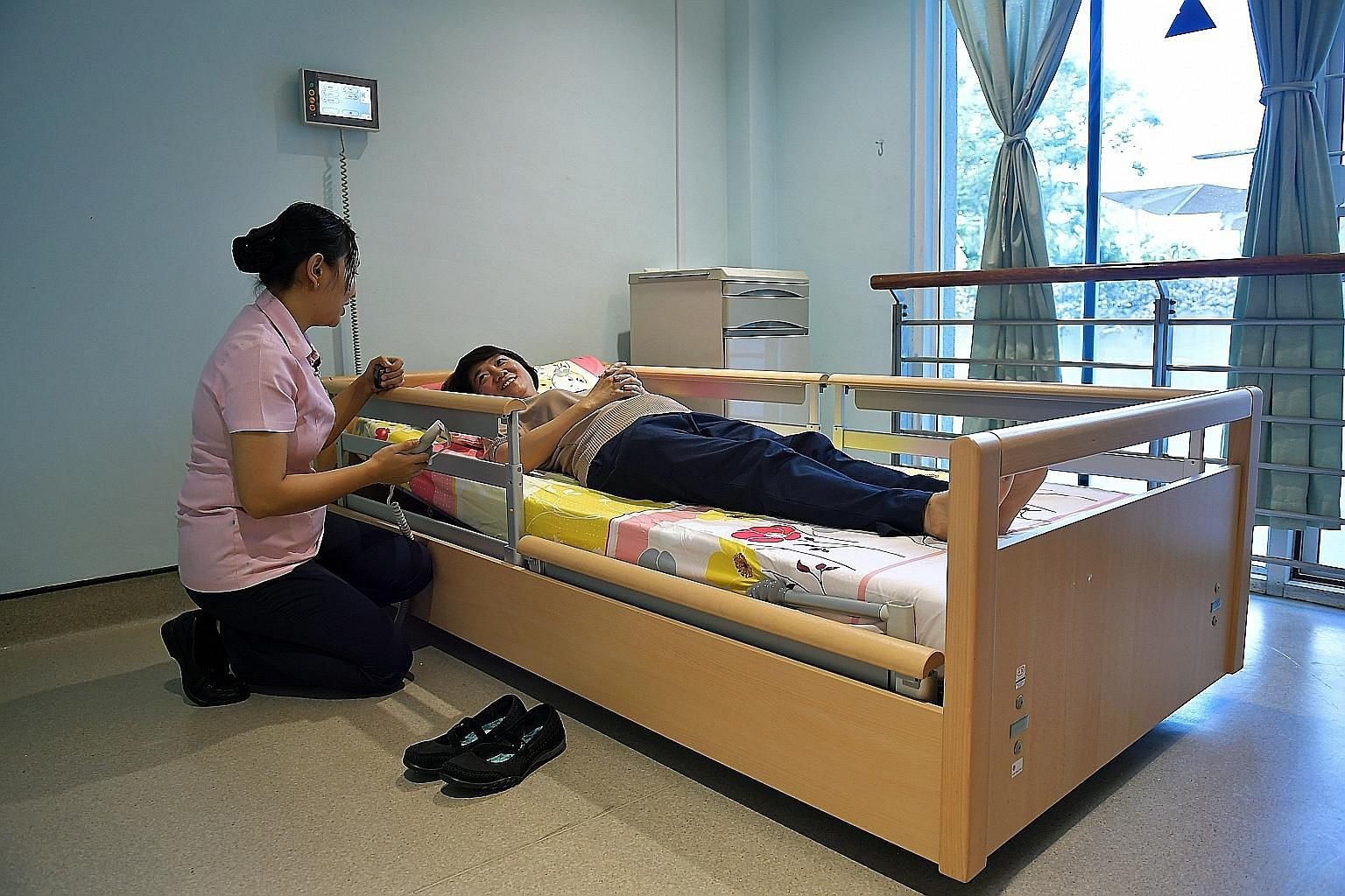 Senior staff nurse Khin Phone Tint, 33, showing how low the new nursing home's bed can go. The bed is designed to prevent a user from getting hurt if he or she falls out of it.