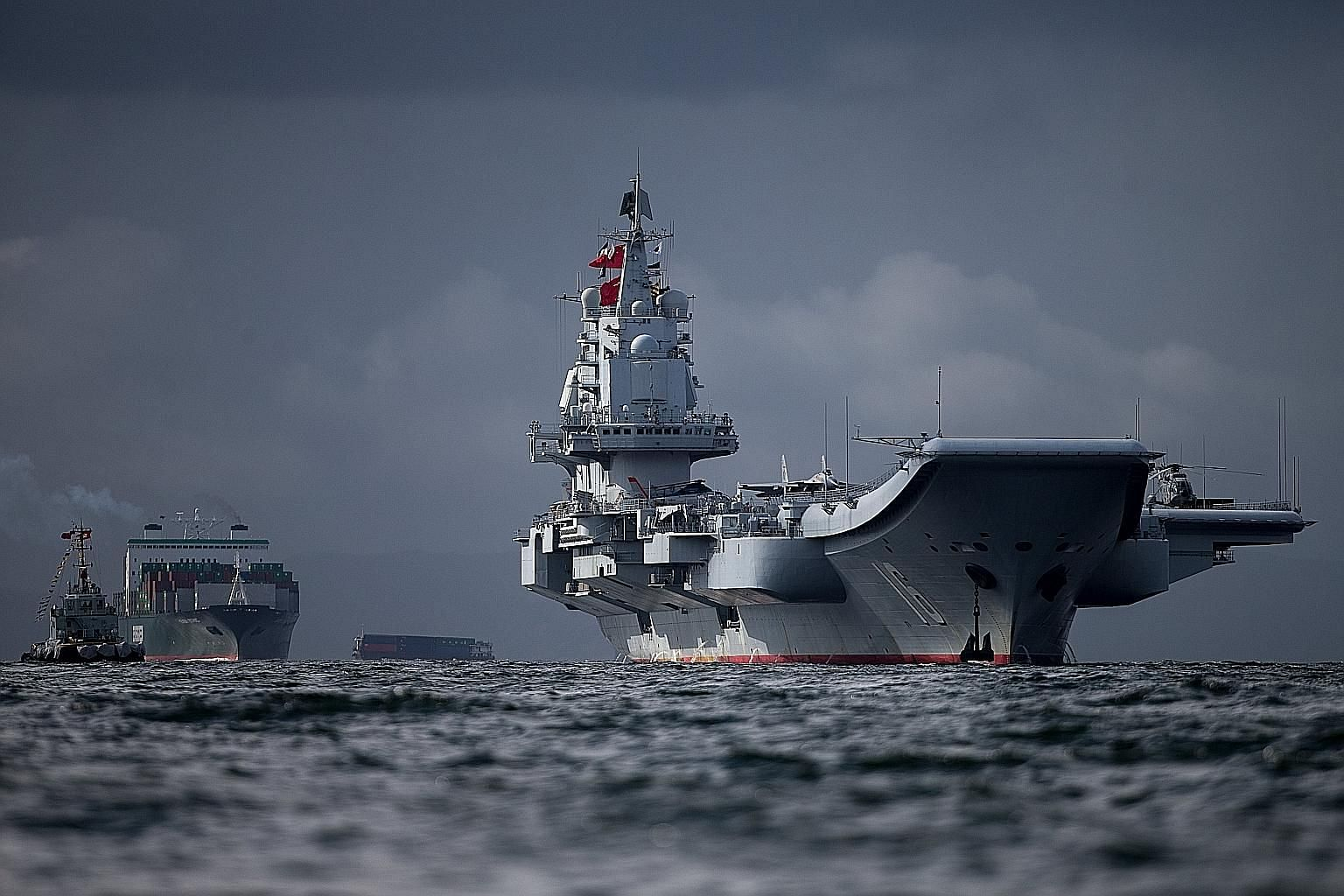 The Liaoning arriving in Hong Kong yesterday. It is accompanied by guided-missile destroyers CNS Jinan and CNS Yinchuan, and guided-missile frigate CNS Yantai, as well as J-15 carrier-borne fighter jets and helicopters in a display of military might