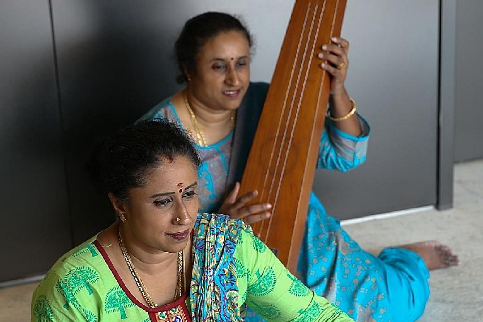 Twin sisters Chandrakala Kunaseelan, holding a double-headed drum called the mridangam, and Shashikala Samugan Nathan, holding a long-necked plucked string instrument called the tambura. The 45-year-old granddaughters of the late percussionist M.V. G