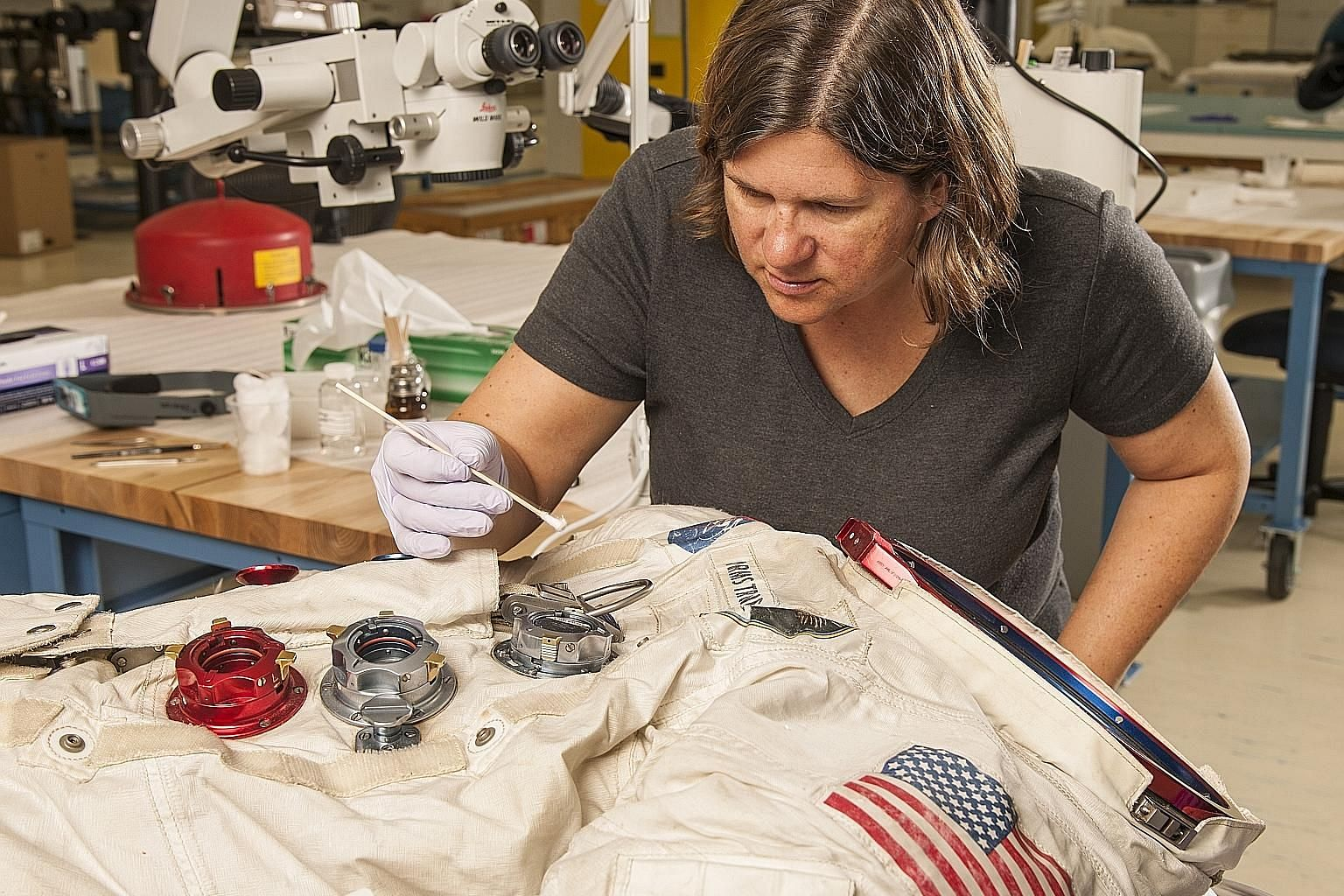 Astronaut Neil Armstrong's spacesuit (above) being worked on in a conservation laboratory; and Dorothy's red slippers from The Wizard Of Oz.
