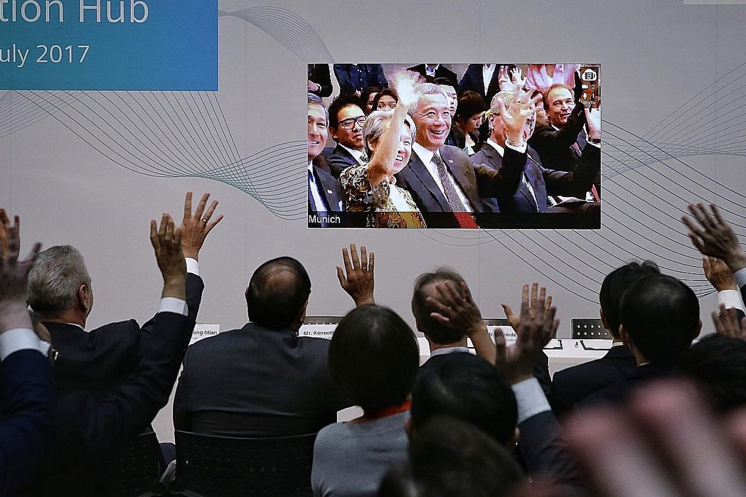 Prime Minister Lee Hsien Loong and Mrs Lee waving over a live video feed from Munich to Minister for Trade and Industry (Industry) S. Iswaran (second from left) and Siemens representatives in Singapore yesterday. PM Lee opened the Siemens Digitalisat