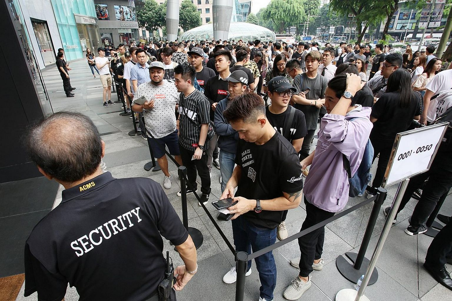 Shoppers wait to enter Louis Vuitton's Ion Orchard boutique yesterday morning.