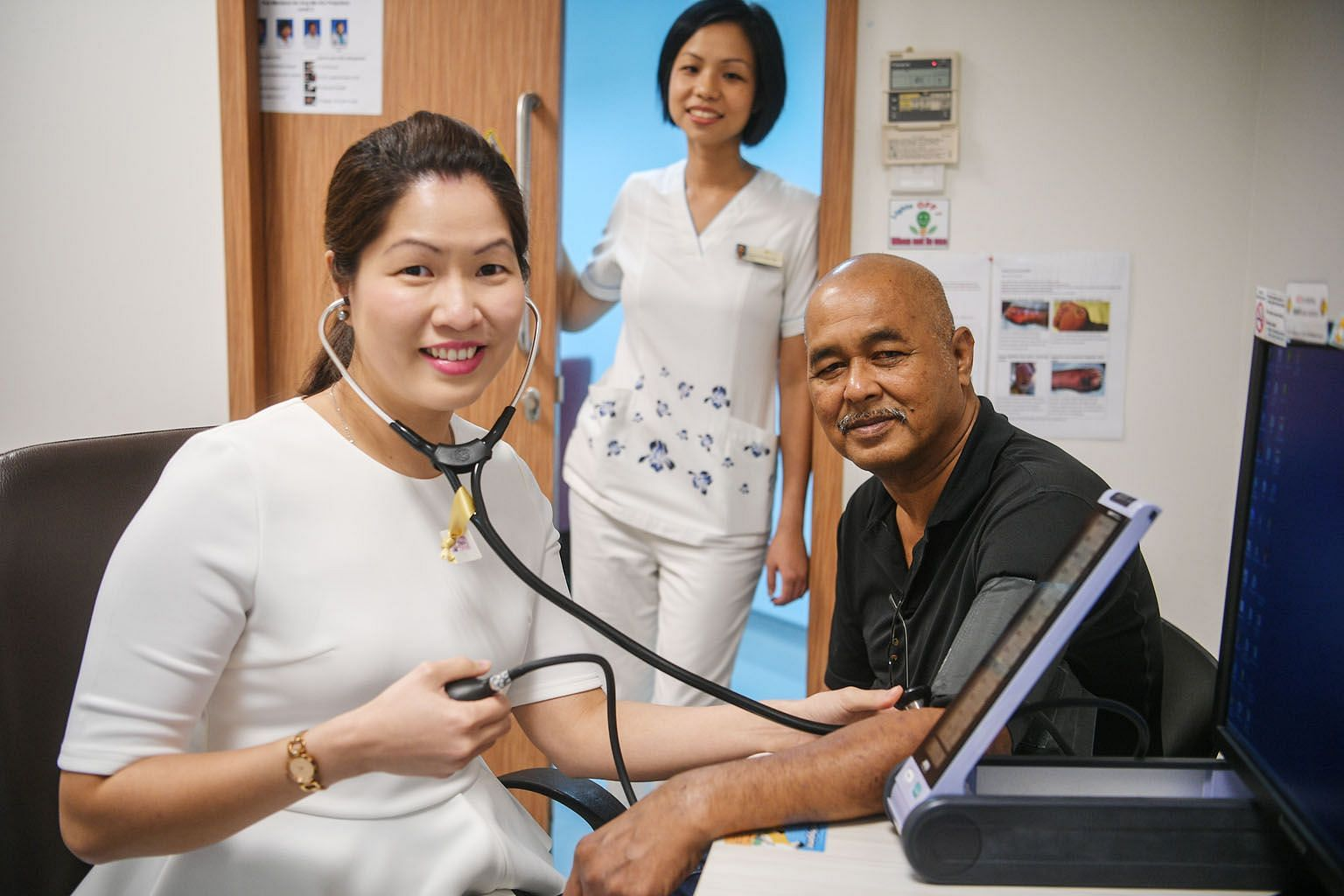 Dr Tricia Chang attending to Mr Adam Salim at Ang Mo Kio Polyclinic, with Senior Staff Nurse Evonne Oh looking on. Dr Chang said patients are more motivated and willing to take charge of their health.