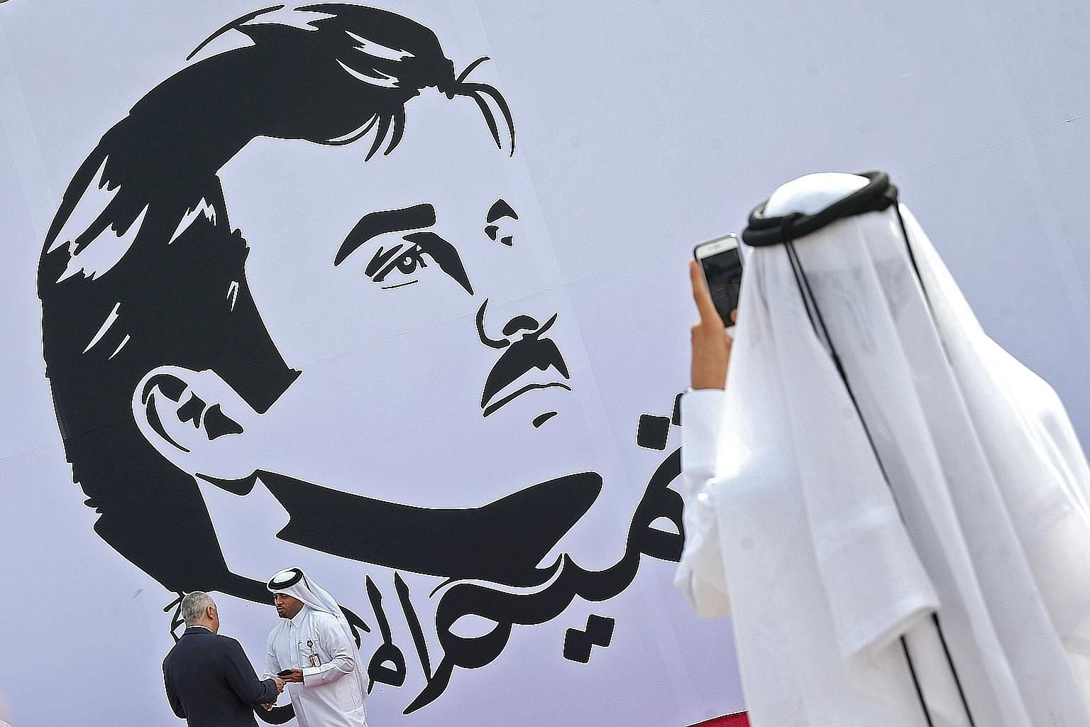 A wall in Doha with a portrait of Qatar's Emir, Sheikh Tamim bin Hamad al-Thani. His image has been appearing on social media, street posters and T-shirts.
