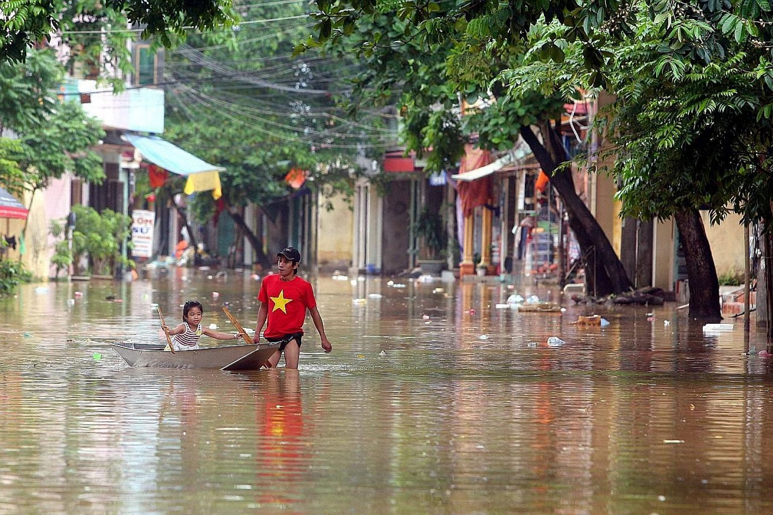 A man pulling a boat with his daughter inside through a flooded street in Yen Bai province, Vietnam, yesterday. More rainfall, measuring 100 to 200mm, is forecast to hit north-east and north central Vietnam in the next few days.