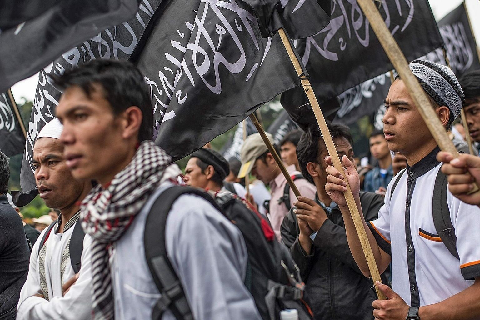 Protesters waving flags of Islamist group Hizbut Tahrir Indonesia (HTI) during a rally in Jakarta on Tuesday, to condemn a decree allowing the Indonesian government to ban groups that oppose its official state ideology. The emergency regulation is wi