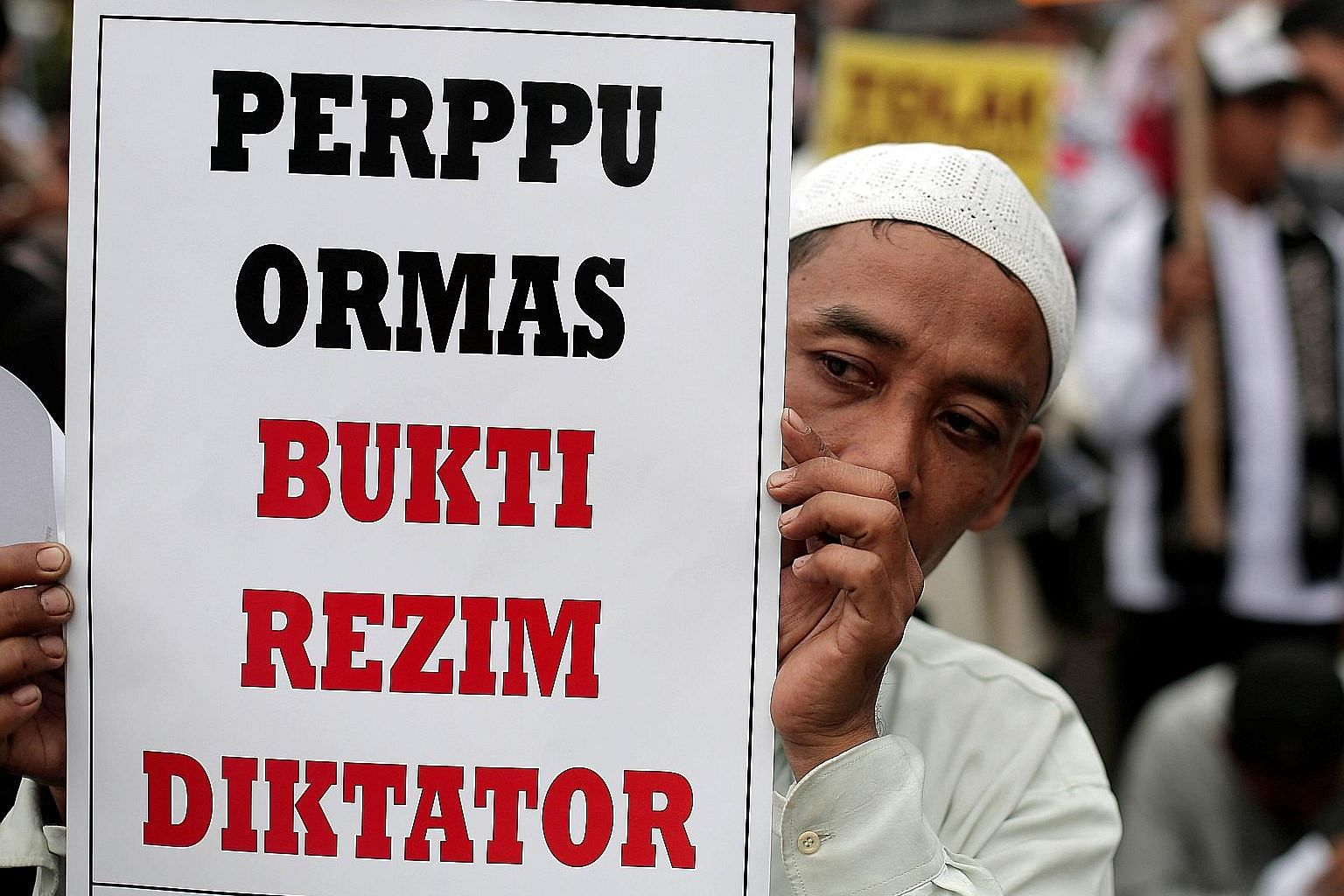 "A protester holding up a placard which reads ""Regulation for mass organisations is evidence of a dictatorial regime"" during a demonstration in Jakarta on Tuesday."