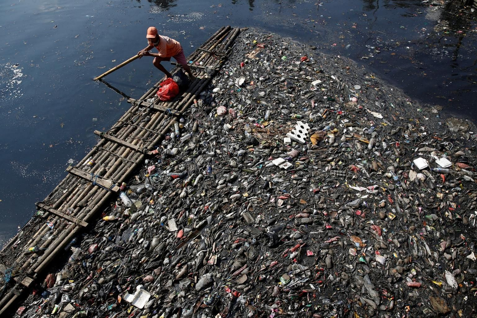 A worker using a raft to gather plastic and other debris for collection and disposal from a river in Jakarta on June 7.