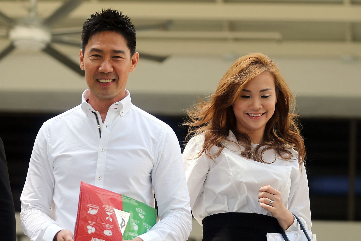 """Mr Edmund Chen and Ms Karen Ho Kai Lun leaving the State Courts yesterday. In a joint statement, they said they had """"mutually and amicably"""" resolved their disputes through mediation."""