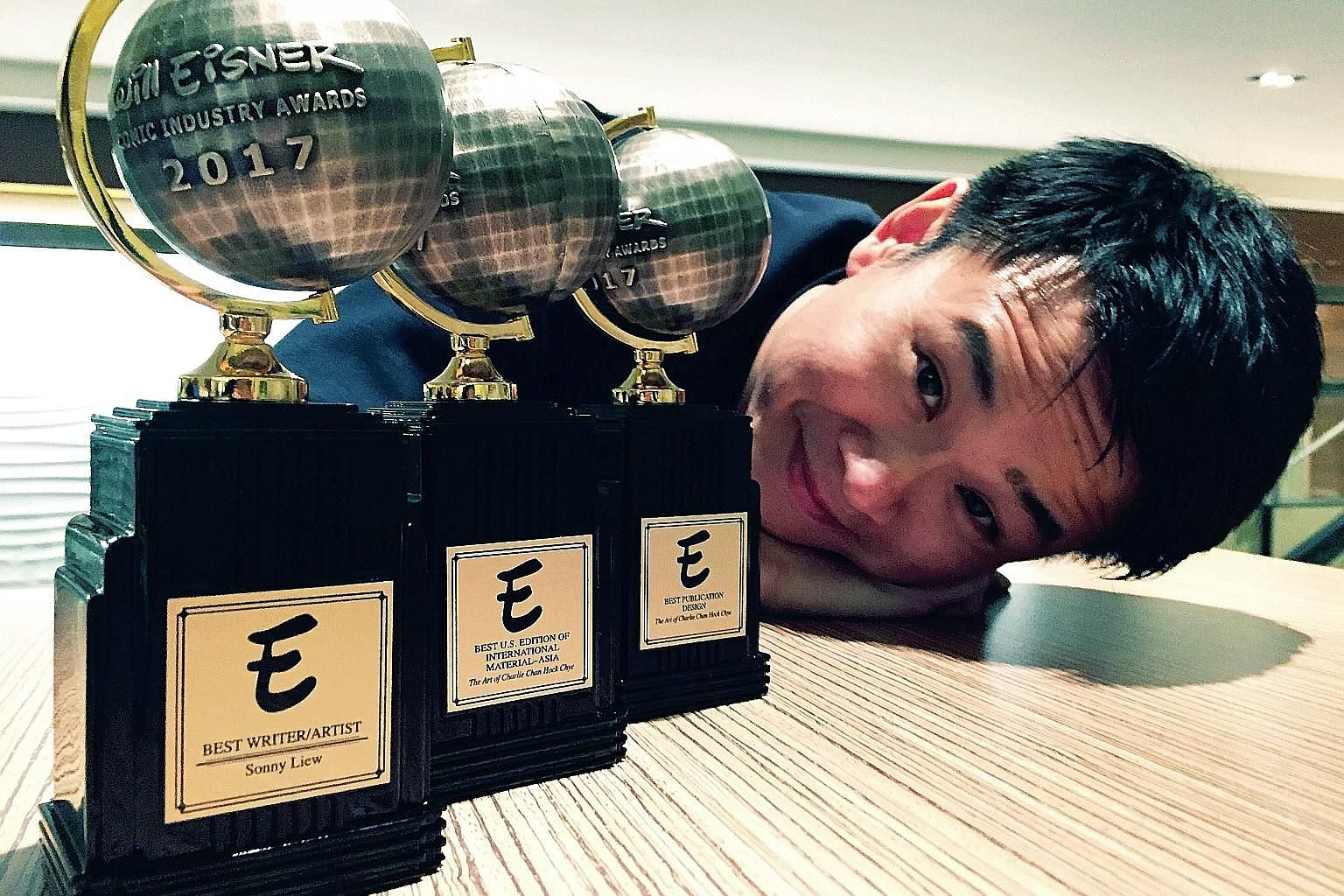 Graphic novelist Sonny Liew with the three Eisner awards he won for his graphic novel, The Art Of Charlie Chan Hock Chye, which retells Singapore's journey to nationhood.