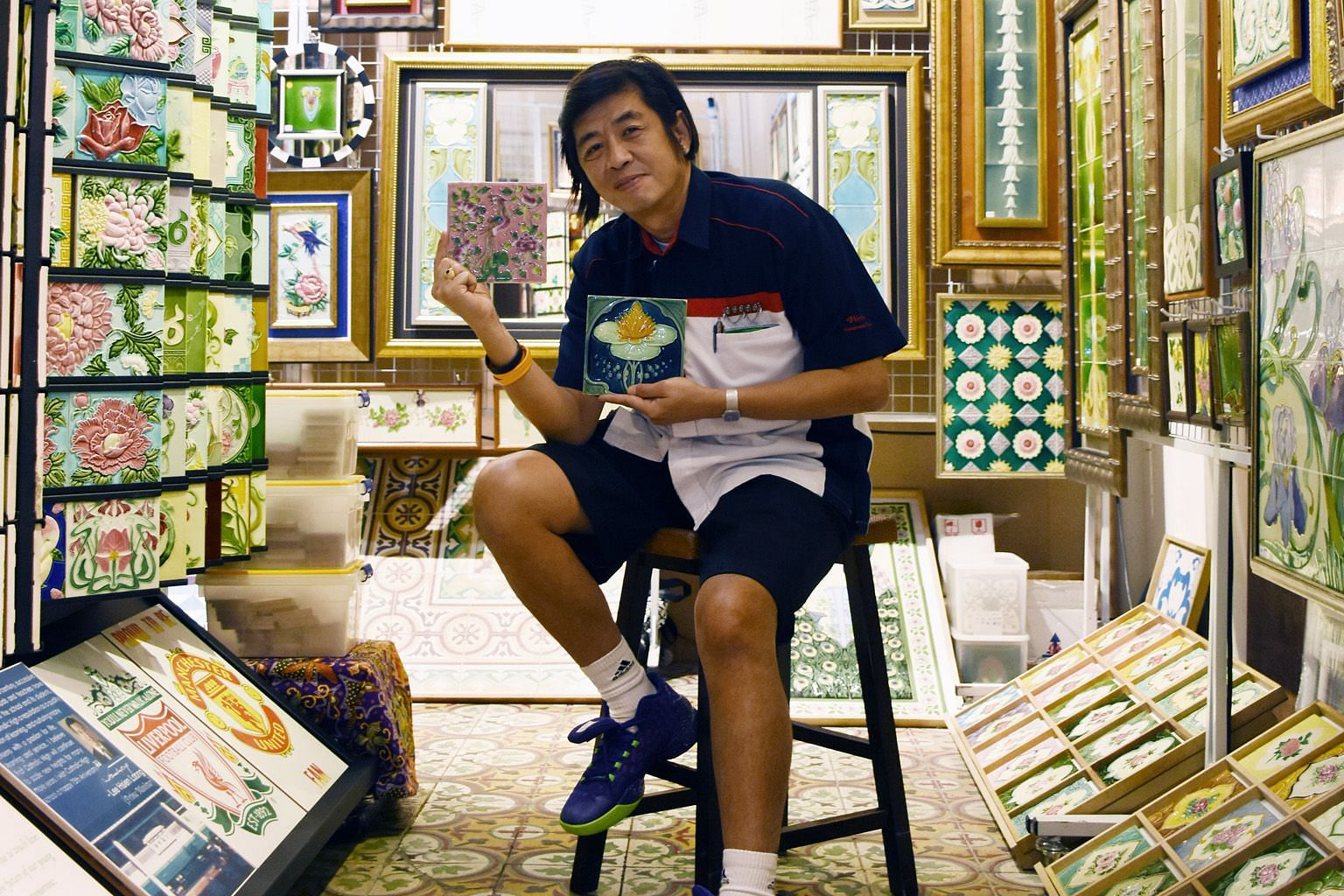 Mr Victor Lim at his Peranakan Tiles Gallery, showing examples of European Art Noveau and Japanese Art Deco tiles.