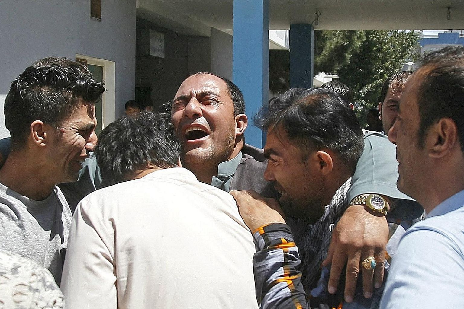 Relatives of the victims of a suicide bomb blast outside a hospital in Kabul, Afghanistan, yesterday. A Taleban suicide attacker set off a car bomb in the western part of Kabul yesterday, killing up to 35 people and wounding more than 40. At least 35