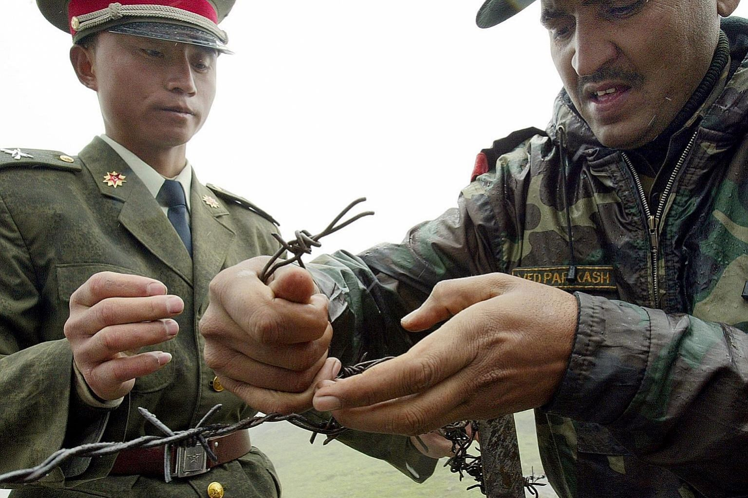 A Chinese soldier and an Indian soldier fixing a barbed-wire fence at the Nathu La border crossing between India and China in India's north-eastern Sikkim state in 2006. China and India have disputes in several areas along a 4,000km border, including