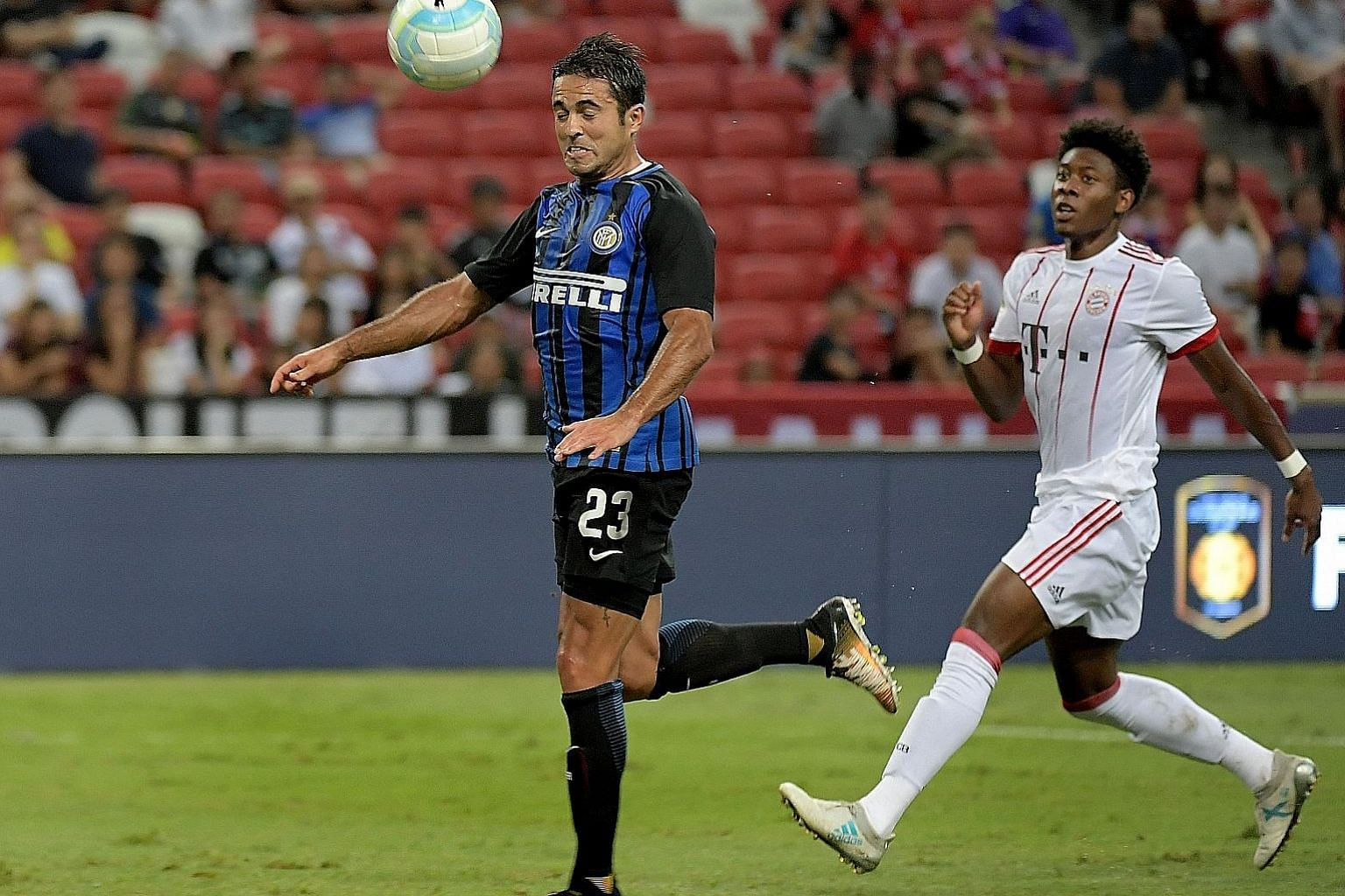 Inter's Eder Martins heading in his second goal against Bayern Munich last night as David Alaba looks on.