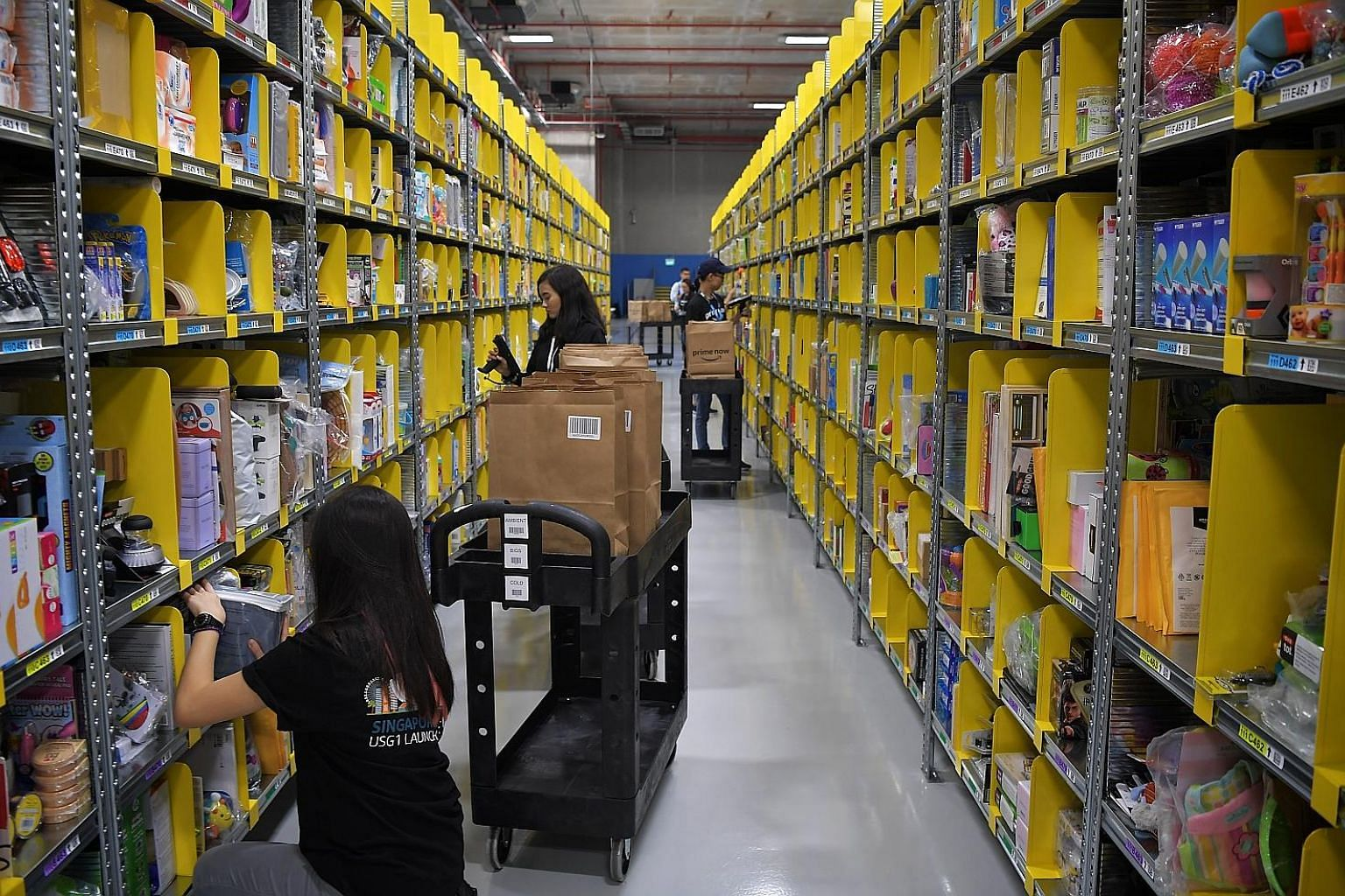 Staff packing orders yesterday at Amazon's Prime Now Fulfilment Centre in Singapore, which is now its largest in the world. Through the Prime Now app, customers can get products delivered to them in two hours.