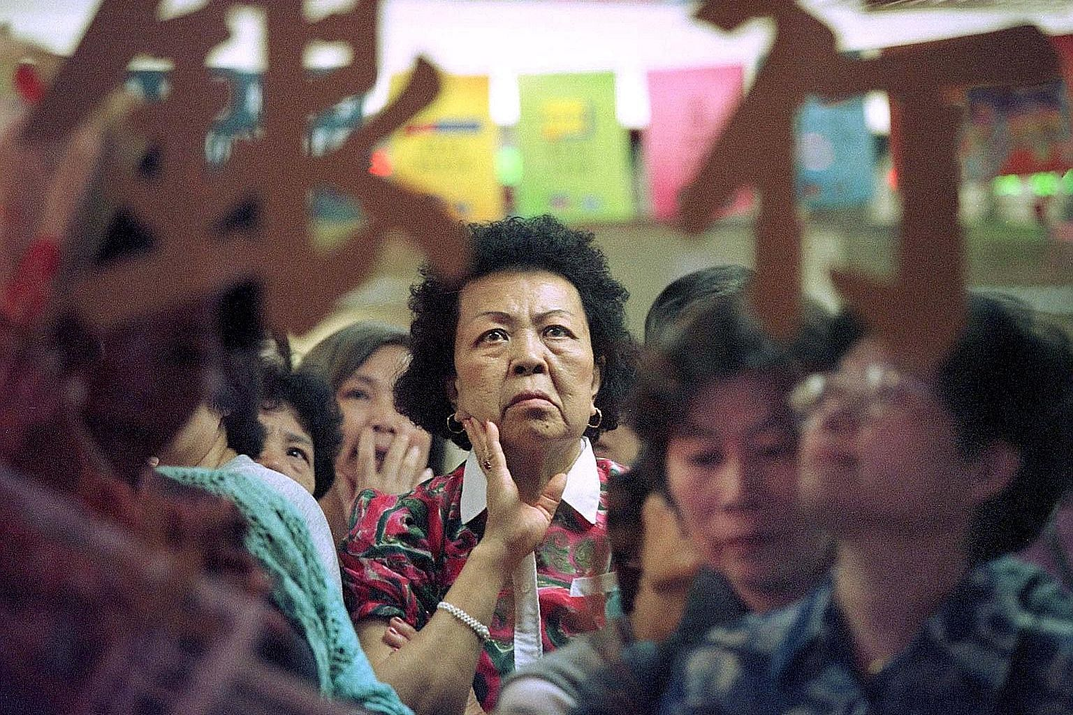 An investor watching share prices in Hong Kong in 1998, during the period of the Asian financial crisis. People must factor in the possibility of such crises happening because the time span for their home mortgage can stretch 20 to 30 years, when man
