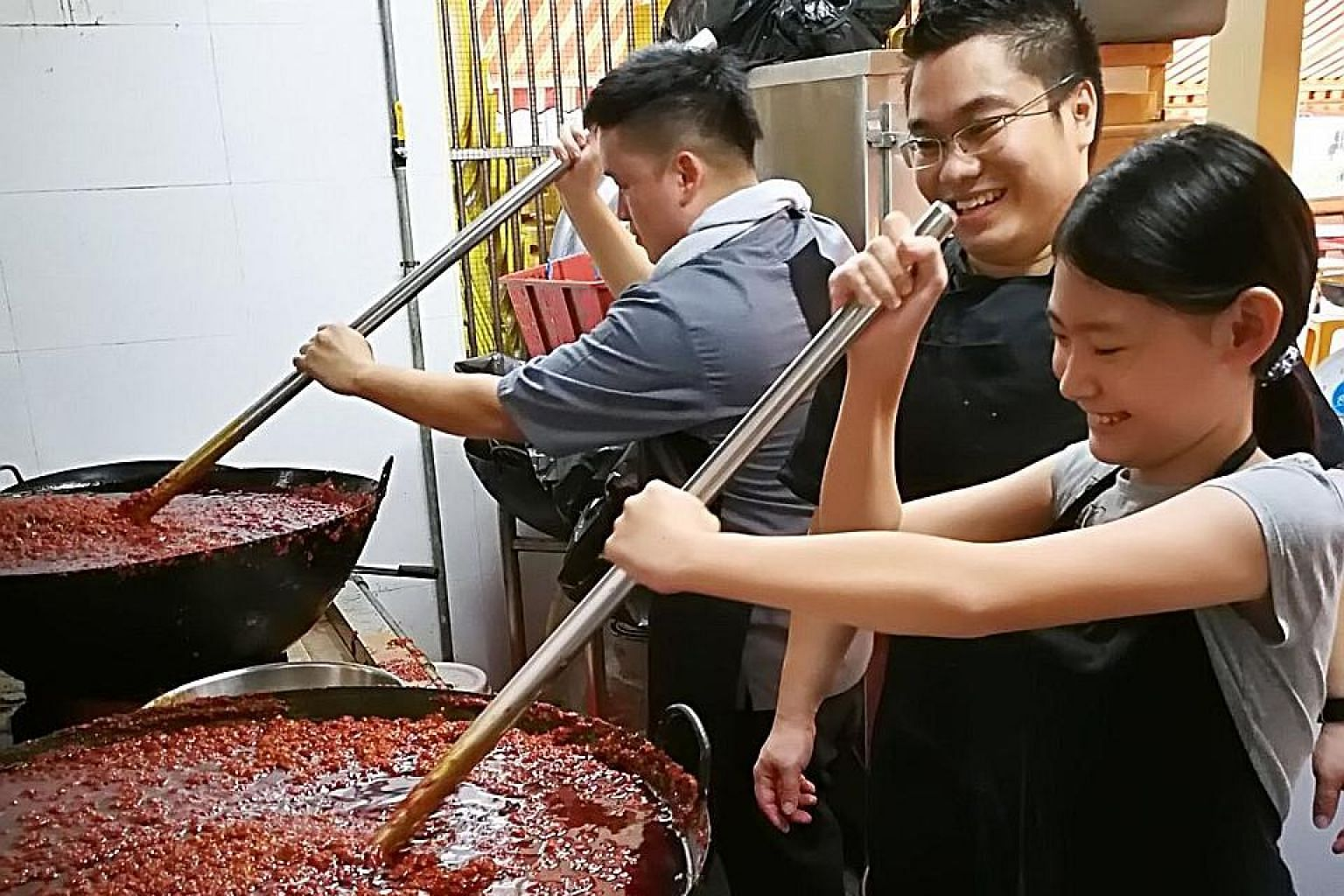 Phoebe working with chef Wayne Liew (below left) of KEK Pandan Gardens and Good Chance Popiah's owner Boon Kai Chun. Her bottled chilli paste (above) costs $15 each.