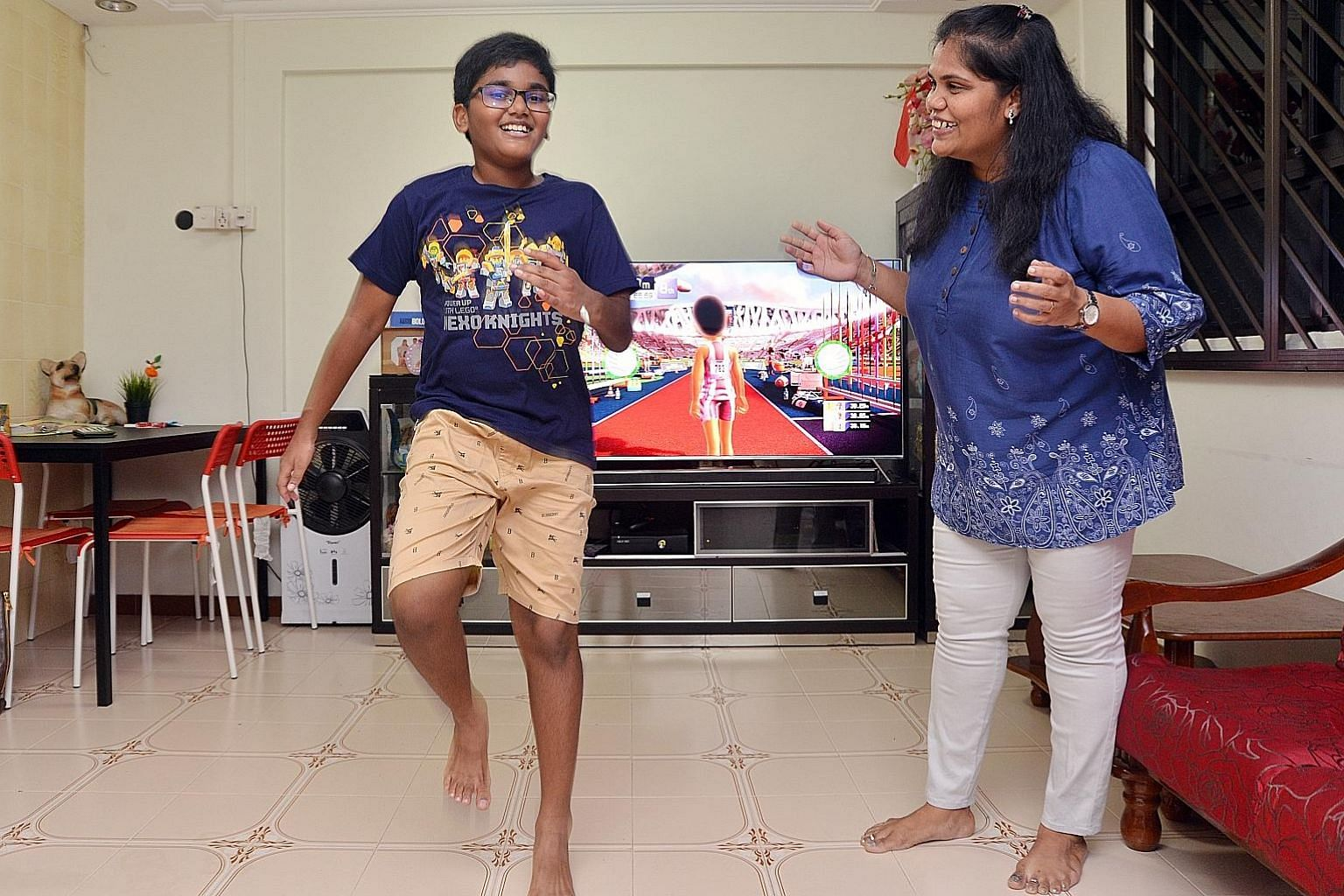 Ramachandran Nikhil, 10, and his mum, IT professional Kasi Kanimozhi. Nikhil is playing a video game that requires him to be active.