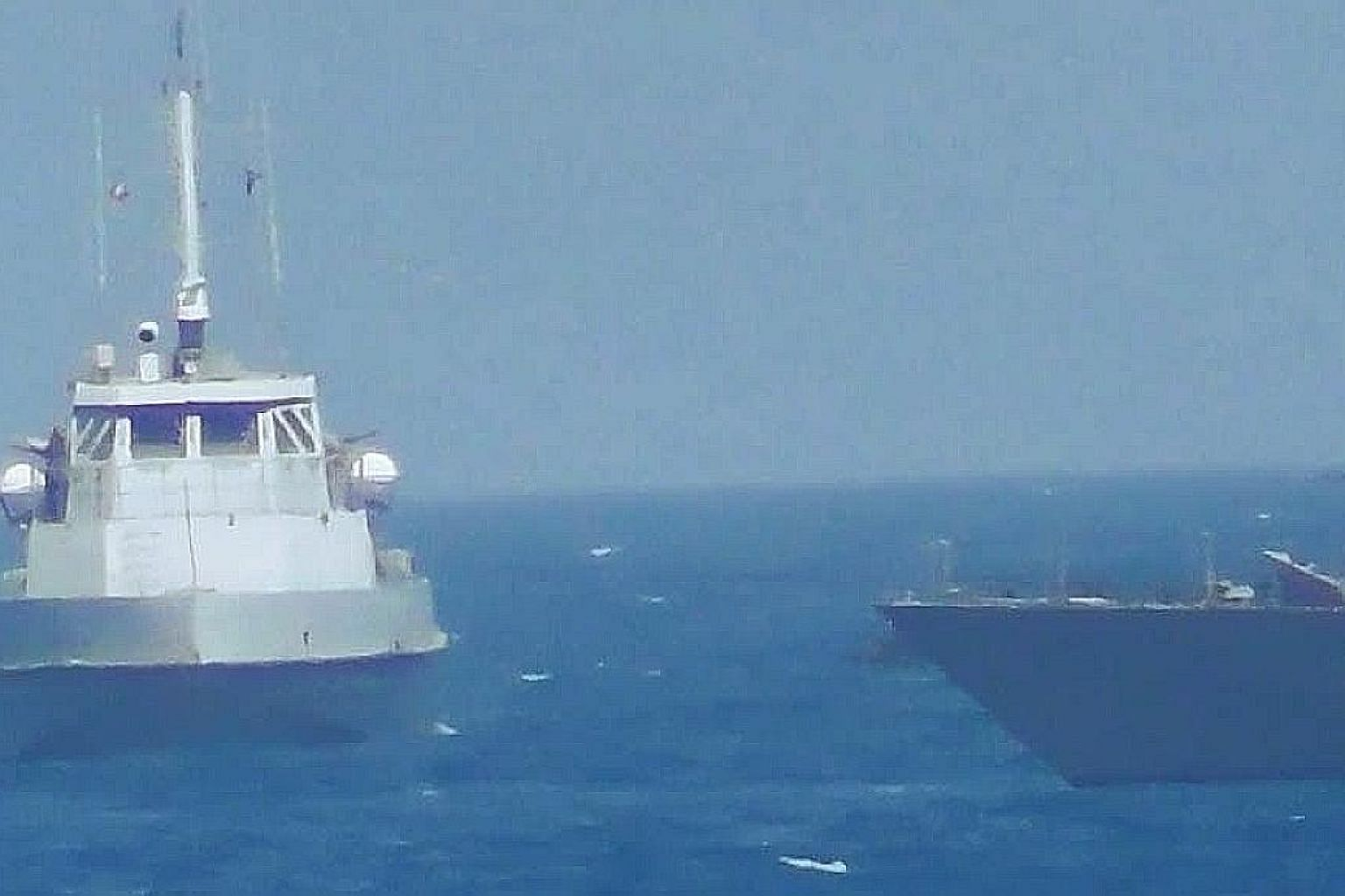 An Iranian naval vessel (left) approaching the coastal patrol ship USS Thunderbolt in the Persian Gulf last Tuesday. According to the US Department of Defence, the USS Thunderbolt fired warning shots near the Iranian ship.