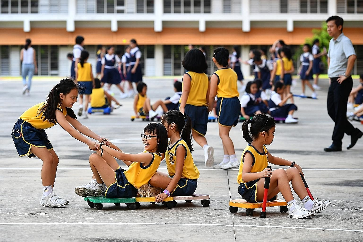 Paya Lebar Methodist Girls' School (Primary) pupils having fun during recess. The school's pupils can borrow equipment such as frisbees, badminton racquets, skipping ropes and roller racers during such breaks, with parent helpers and school staff on