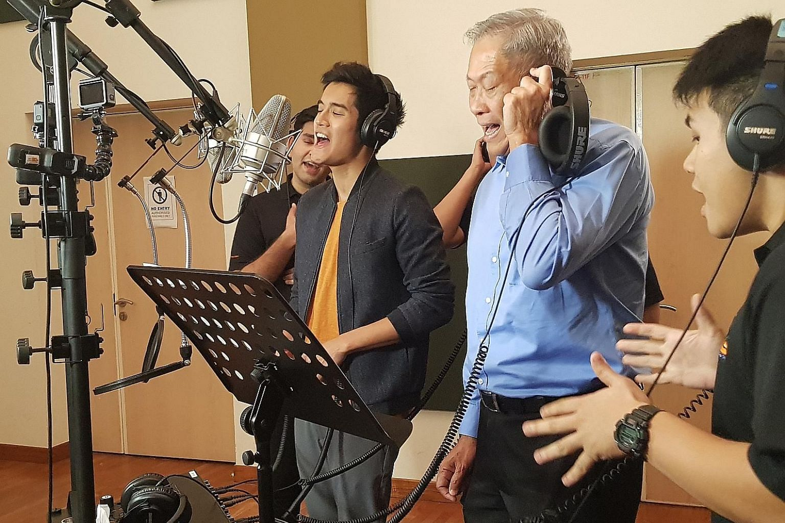 Singer Nathan Hartono, Defence Minister Ng Eng Hen and vocalist group Camokakis (in black) at a recording session last Tuesday for We Are The People, one of the tracks in the NS50 album to be released during NS50 Week.