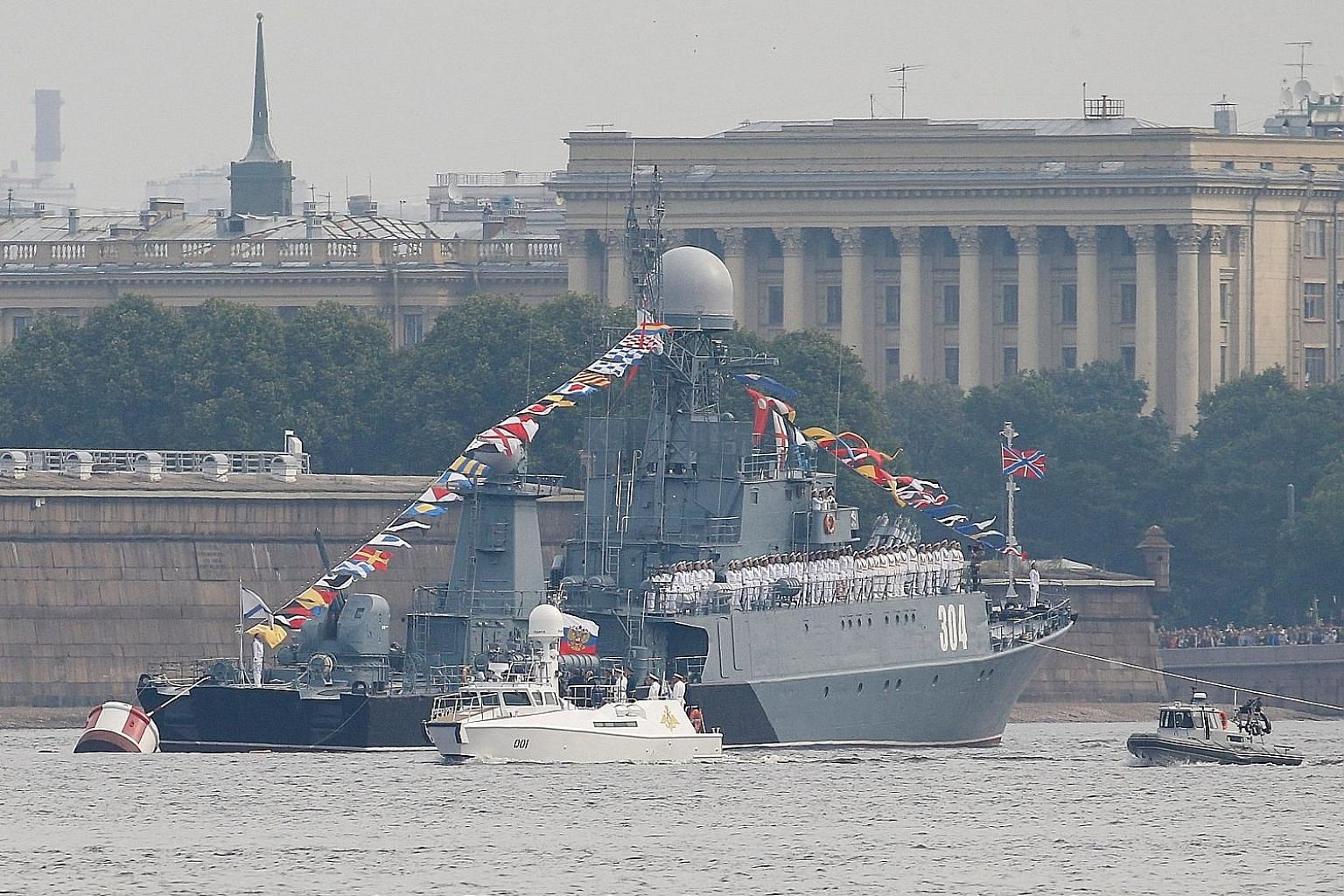 Russian President Vladimir Putin overseeing the Navy Day parade on board his white presidential cutter along the Neva River near St Petersburg yesterday.