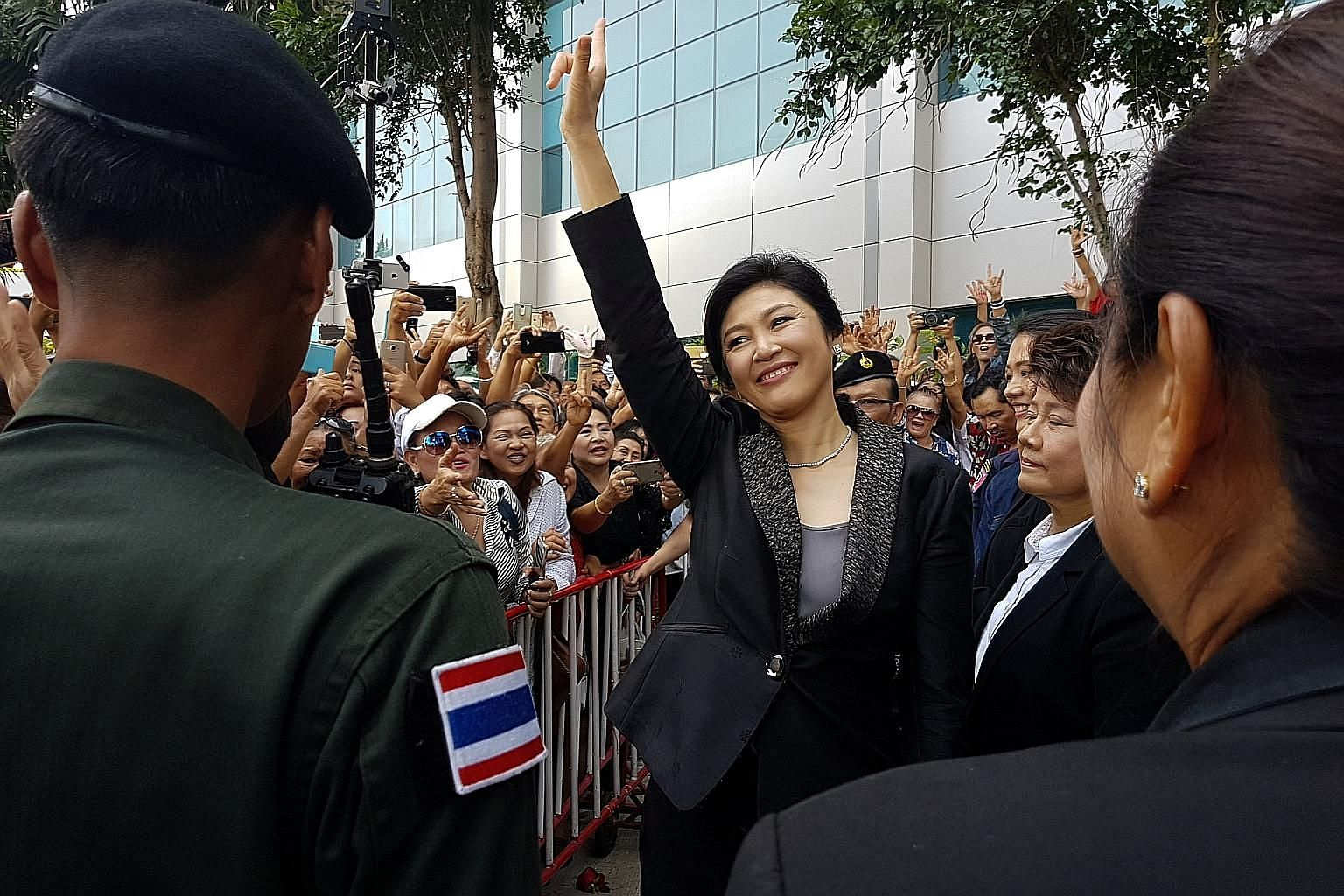 Ousted Thai prime minister Yingluck Shinawatra greeting supporters on leaving the Supreme Court in Bangkok yesterday.