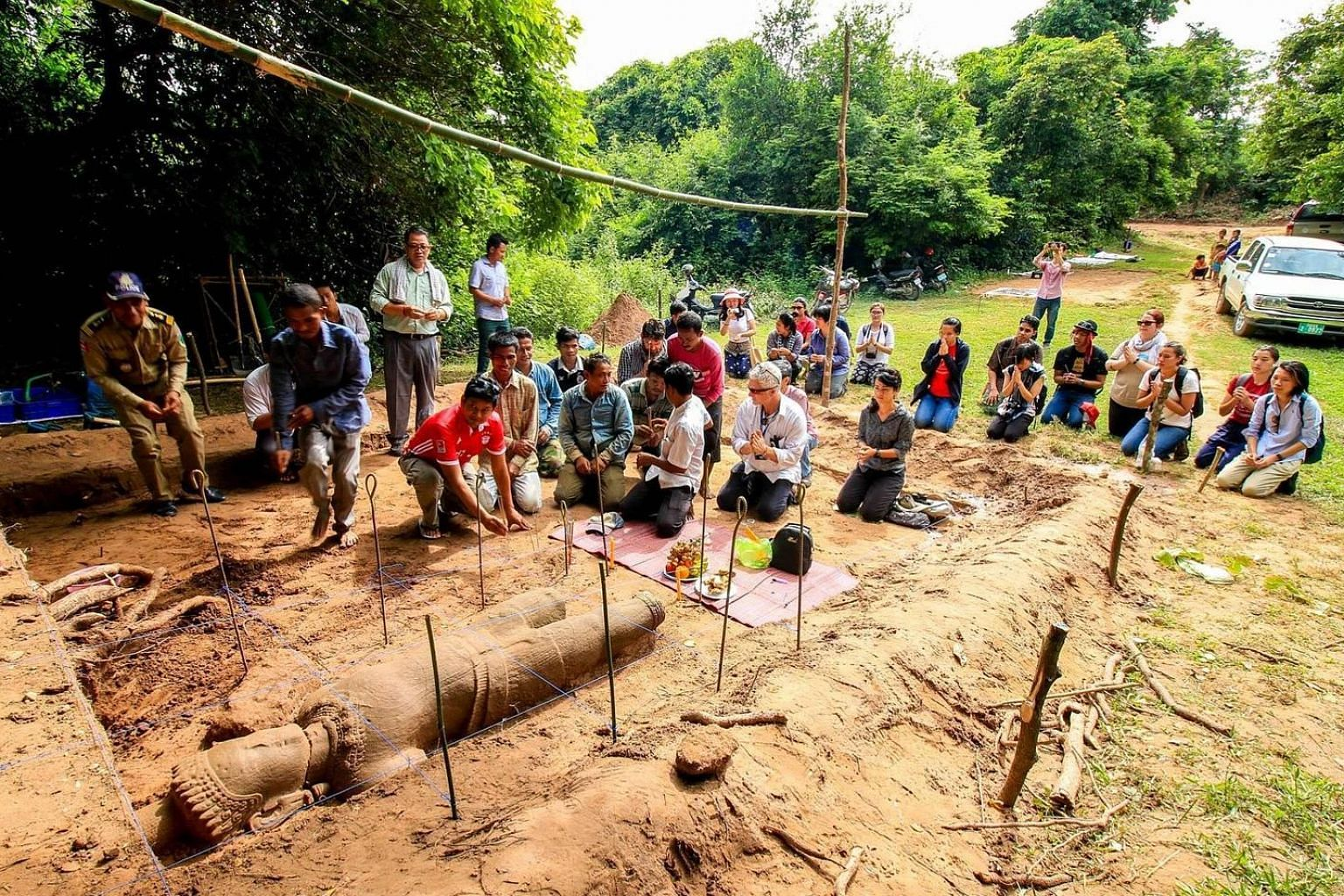 The field team from ISEAS - Yusof Ishak Institute's Nalanda- Sriwijaya Centre, led by Dr Kyle Latinis, with members of other teams at the site of the dig. Buried in a pit about 40cm deep, the approximately 2m-tall sandstone statue, sculpted in the im