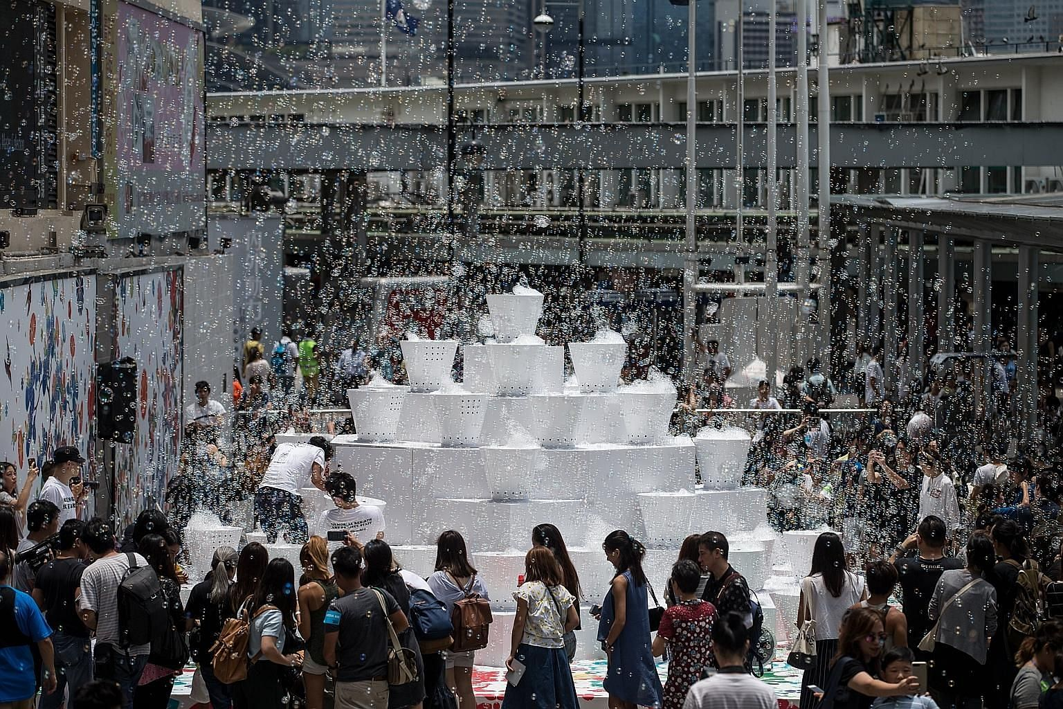 Guests and passers-by are thrilled at the sight of soap bubbles rising in the air during the showcase of an art installation outside Harbour City in Hong Kong yesterday. The art installation, titled Bubble Up, is designed by Japanese artist Shinji Oh