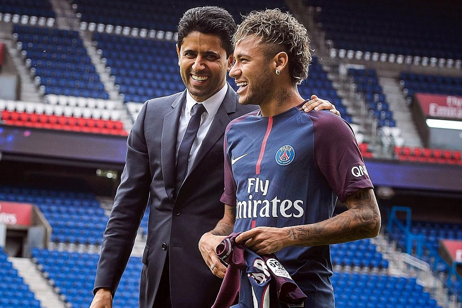 Paris-Saint Germain's chairman and chief executive Nasser Al-Khelaifi and Brazilian striker Neymar are all smiles after a press conference at the Parc des Princes stadium yesterday.