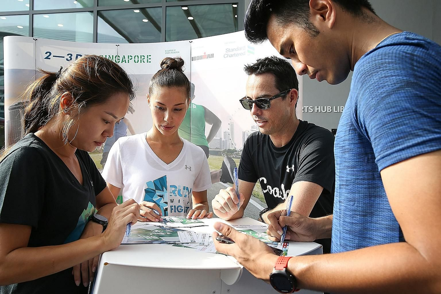 Under Armour Ambassadors Yang Man Yun (far left), Denise Keller (2nd from left) and SCSM Ambassador Joakim Gomez (right) getting zoning advice from running coach Ben Pulham.