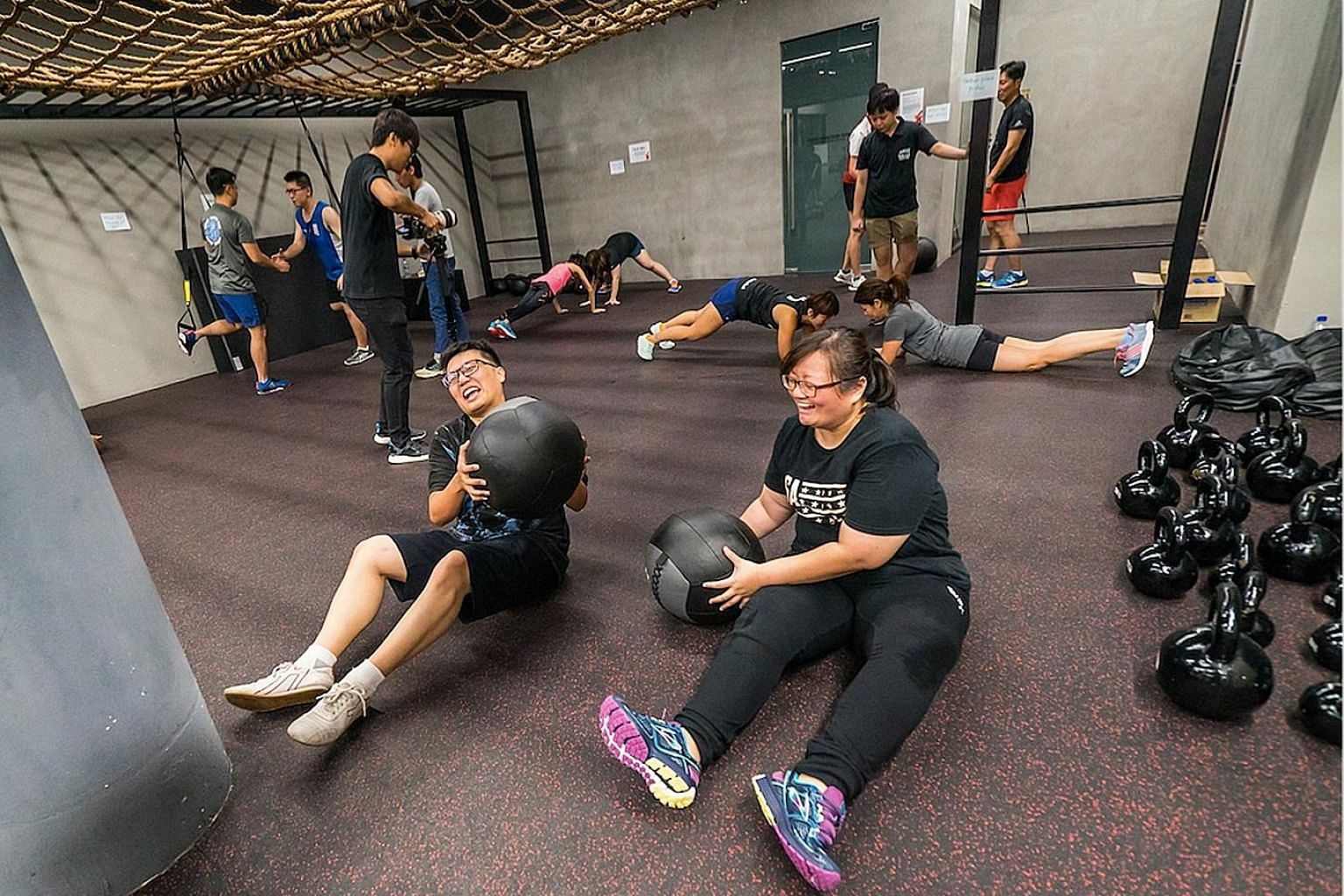 Christine Lim (right) and her husband Wallace Tan working out with medicine balls during the Polar Fitness Bootcamp at TripleFit.